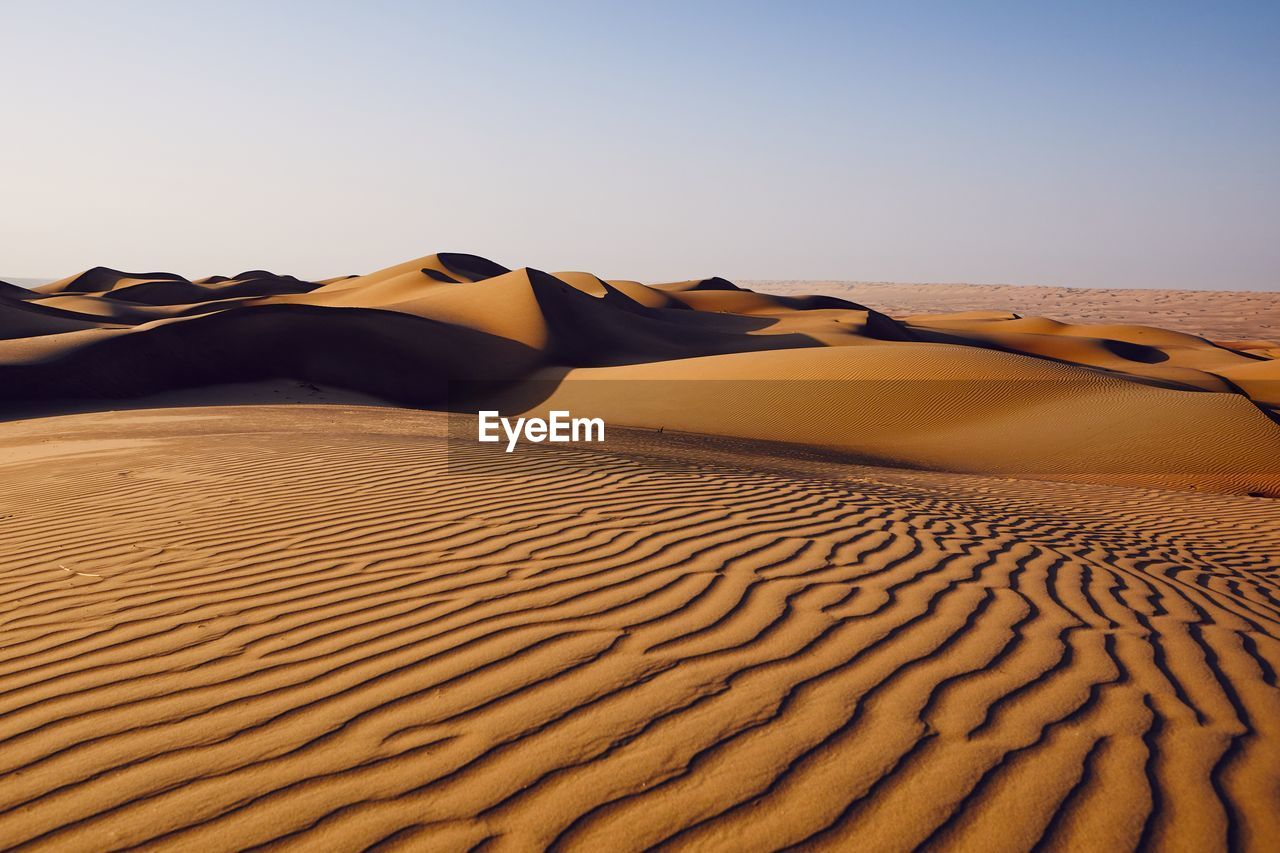 Scenic View Of Desert Against Clear Sky During Sunny Day