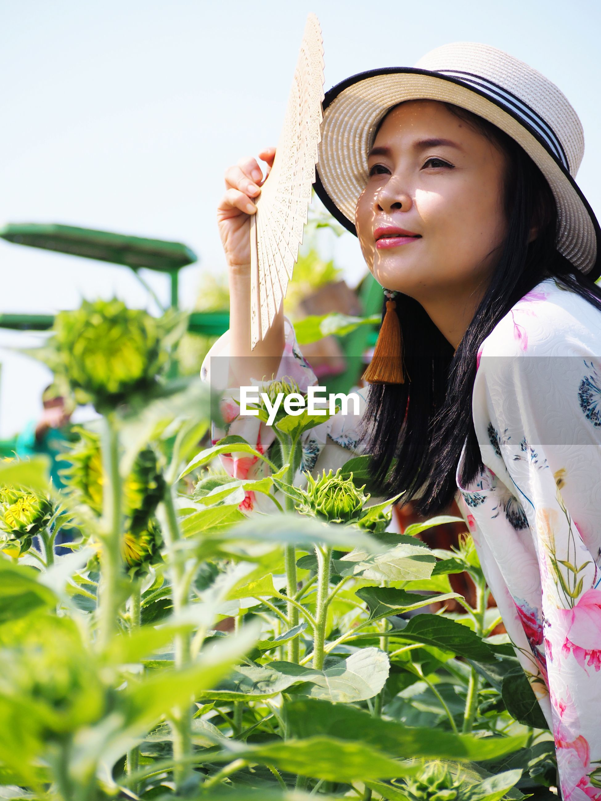 Smiling woman holding hand fan by plants