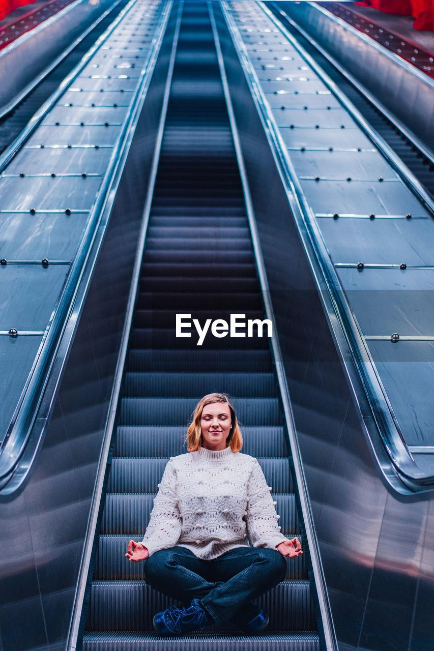 Woman meditating while sitting on escalator