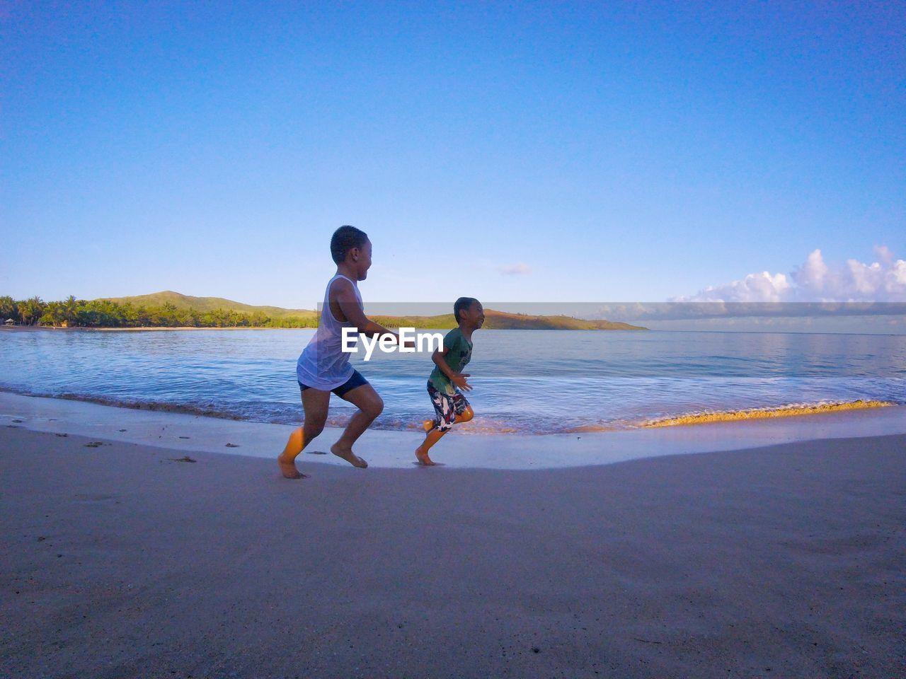 BOY ON BEACH AGAINST SKY