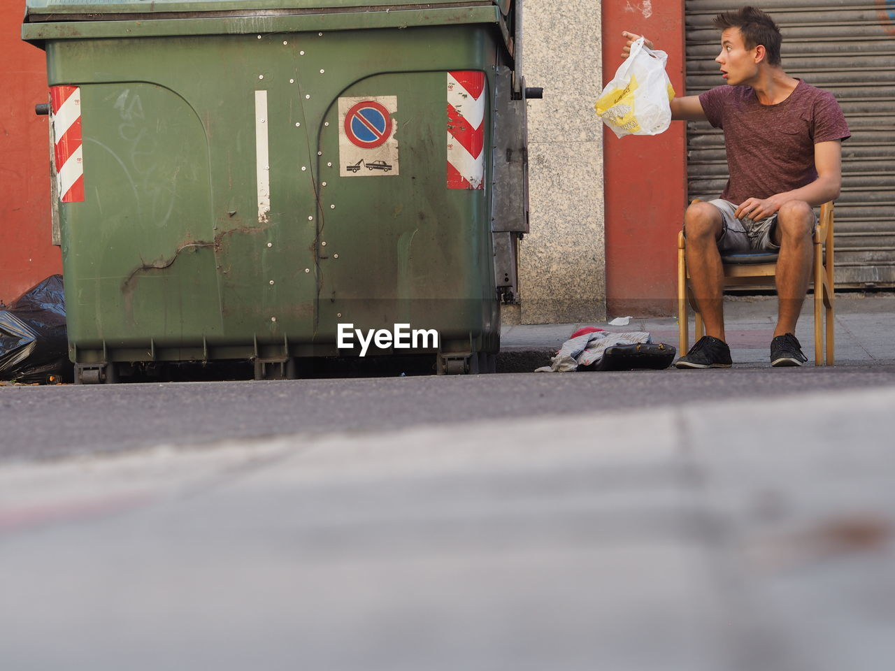 Surface Level Of Young Man Looking At Plastic Bag By Garbage Bin