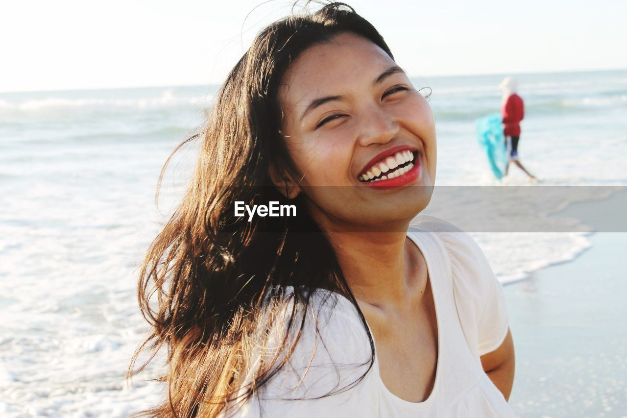 sea, beach, horizon over water, water, real people, nature, leisure activity, one person, smiling, outdoors, sand, fun, vacations, lifestyles, happiness, focus on foreground, day, young women, young adult, scenics, portrait, beauty in nature, wave, sky, close-up