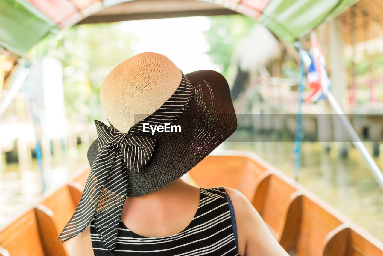 one person, hat, real people, clothing, headshot, focus on foreground, sun hat, lifestyles, leisure activity, portrait, day, men, sitting, chair, seat, striped, looking, adult, close-up, obscured face