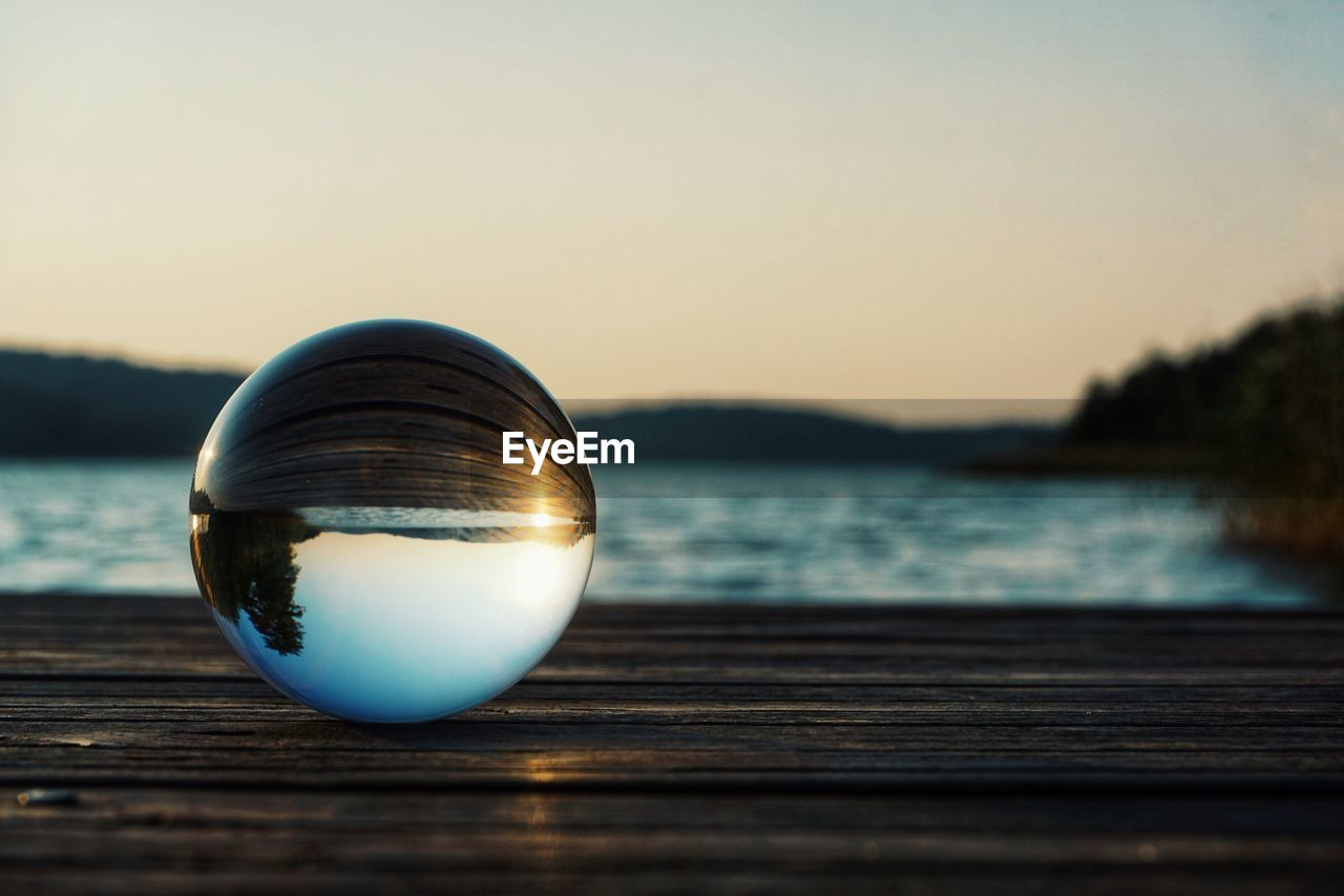 water, sky, sunset, wood - material, scenics - nature, nature, tranquil scene, reflection, selective focus, lake, crystal ball, beauty in nature, sphere, no people, glass - material, clear sky, close-up, outdoors, tranquility