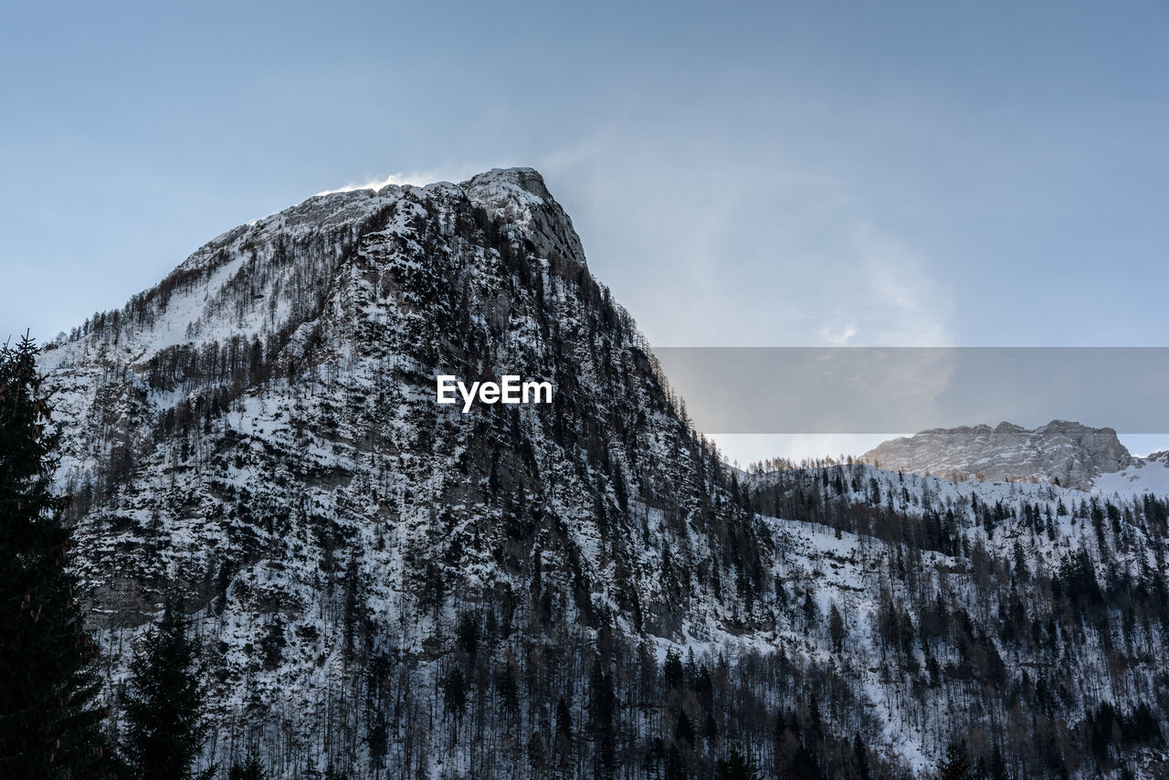 mountain, sky, beauty in nature, scenics - nature, snow, cold temperature, tranquil scene, rock, tranquility, no people, nature, winter, non-urban scene, day, mountain range, solid, rock - object, low angle view, tree, outdoors, mountain peak, formation, snowcapped mountain, eroded