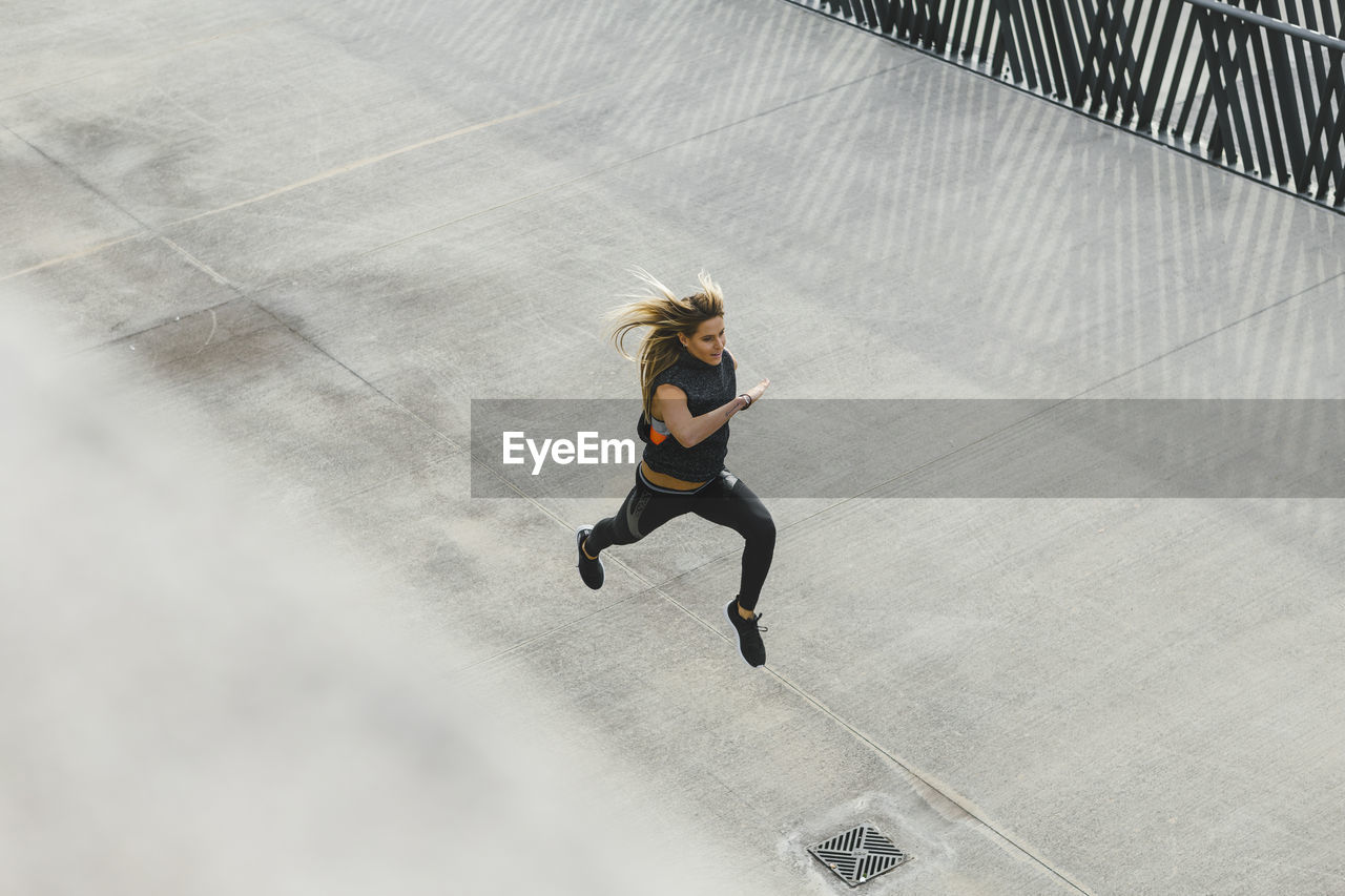 High Angle View Of Woman Running On Footpath