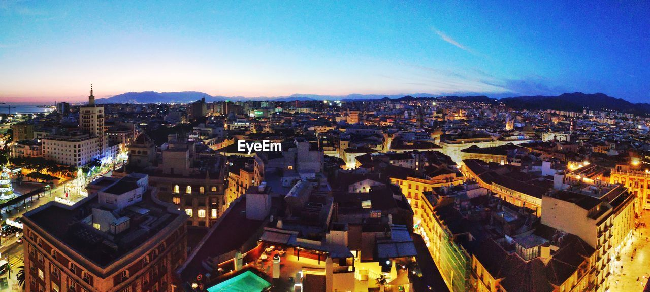 city, building exterior, architecture, cityscape, built structure, sky, crowd, crowded, high angle view, illuminated, building, nature, residential district, city life, night, outdoors, dusk, aerial view, office building exterior, townscape