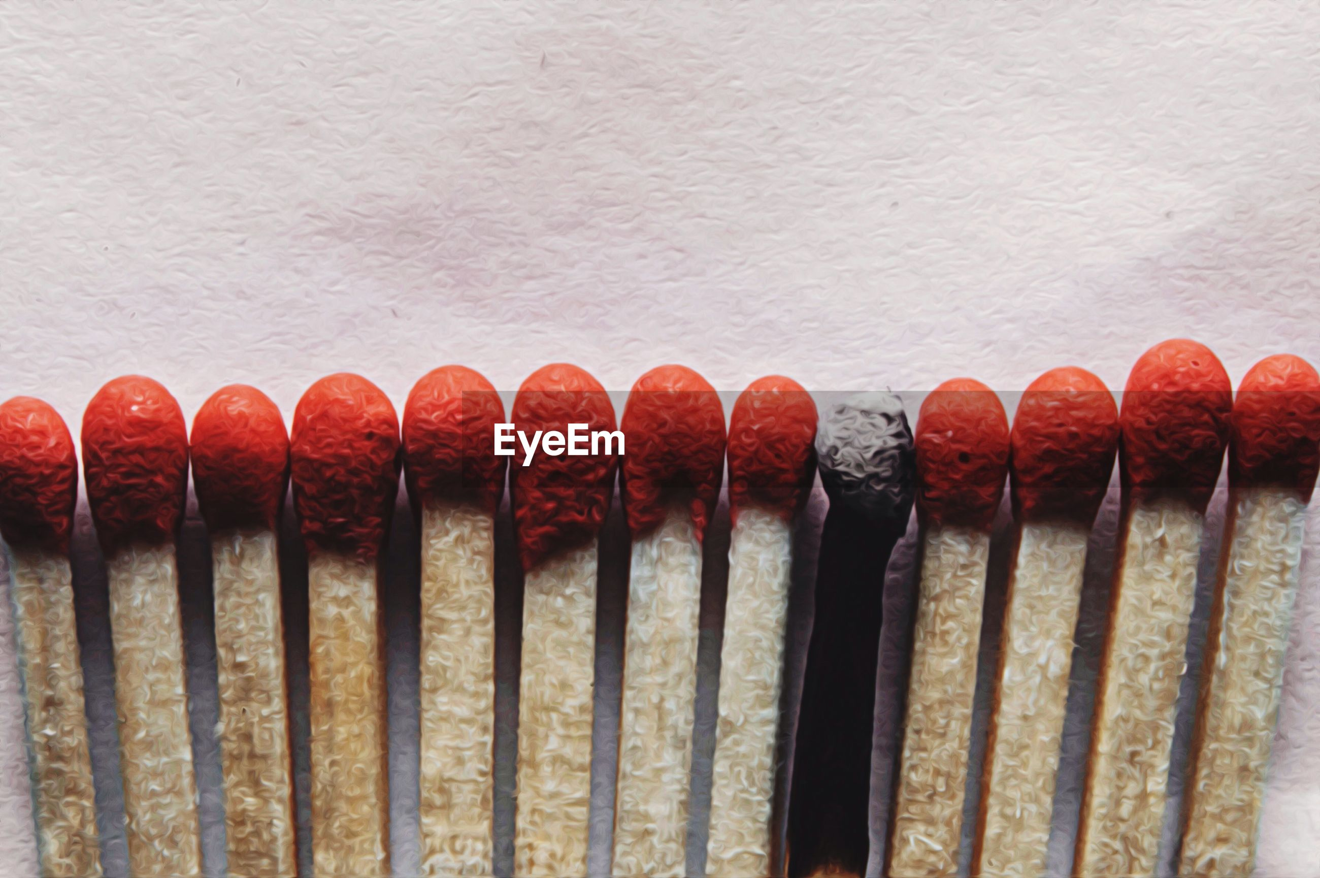 Row of matchsticks with one burnt