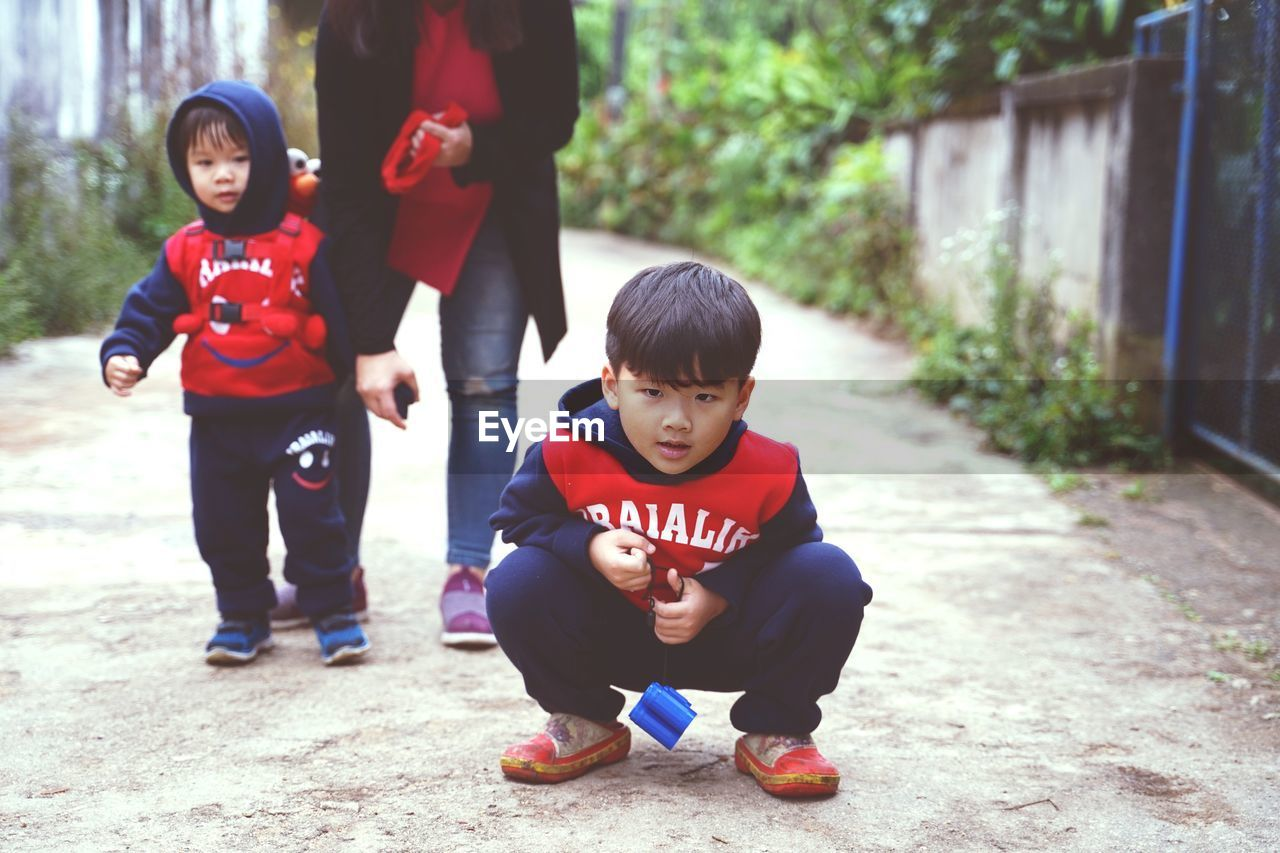 childhood, child, boys, males, men, full length, real people, family, togetherness, females, cute, looking at camera, emotion, casual clothing, portrait, leisure activity, day, bonding, innocence, sister, son, outdoors, daughter