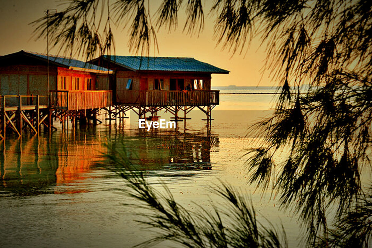 water, outdoors, nature, sunset, stilt house, built structure, waterfront, tranquil scene, sea, reflection, tranquility, scenics, architecture, building exterior, sky, beauty in nature, silhouette, no people, palm tree, clear sky, day, tree