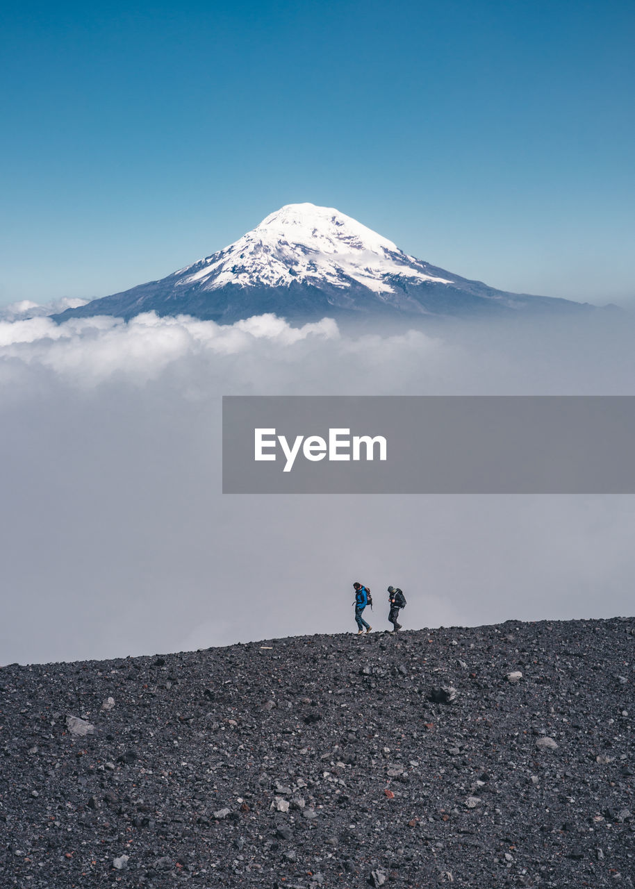 mountain, sky, scenics - nature, beauty in nature, environment, nature, landscape, real people, winter, snowcapped mountain, non-urban scene, volcano, day, land, tranquil scene, tranquility, cold temperature, two people, leisure activity, outdoors, mountain peak