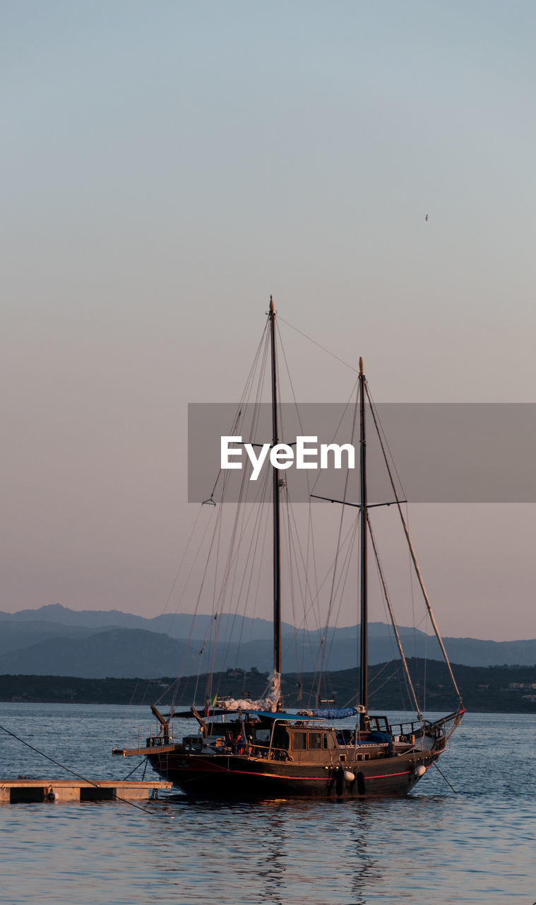 nautical vessel, transportation, water, sky, mode of transportation, sailboat, waterfront, sea, nature, pole, clear sky, mast, sunset, beauty in nature, outdoors, sailing, copy space, day, no people, fishing industry, fishing boat