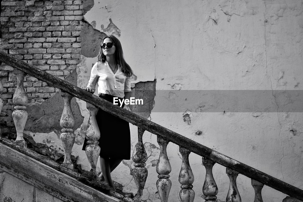 Woman Standing On Staircase Of Abandoned Building