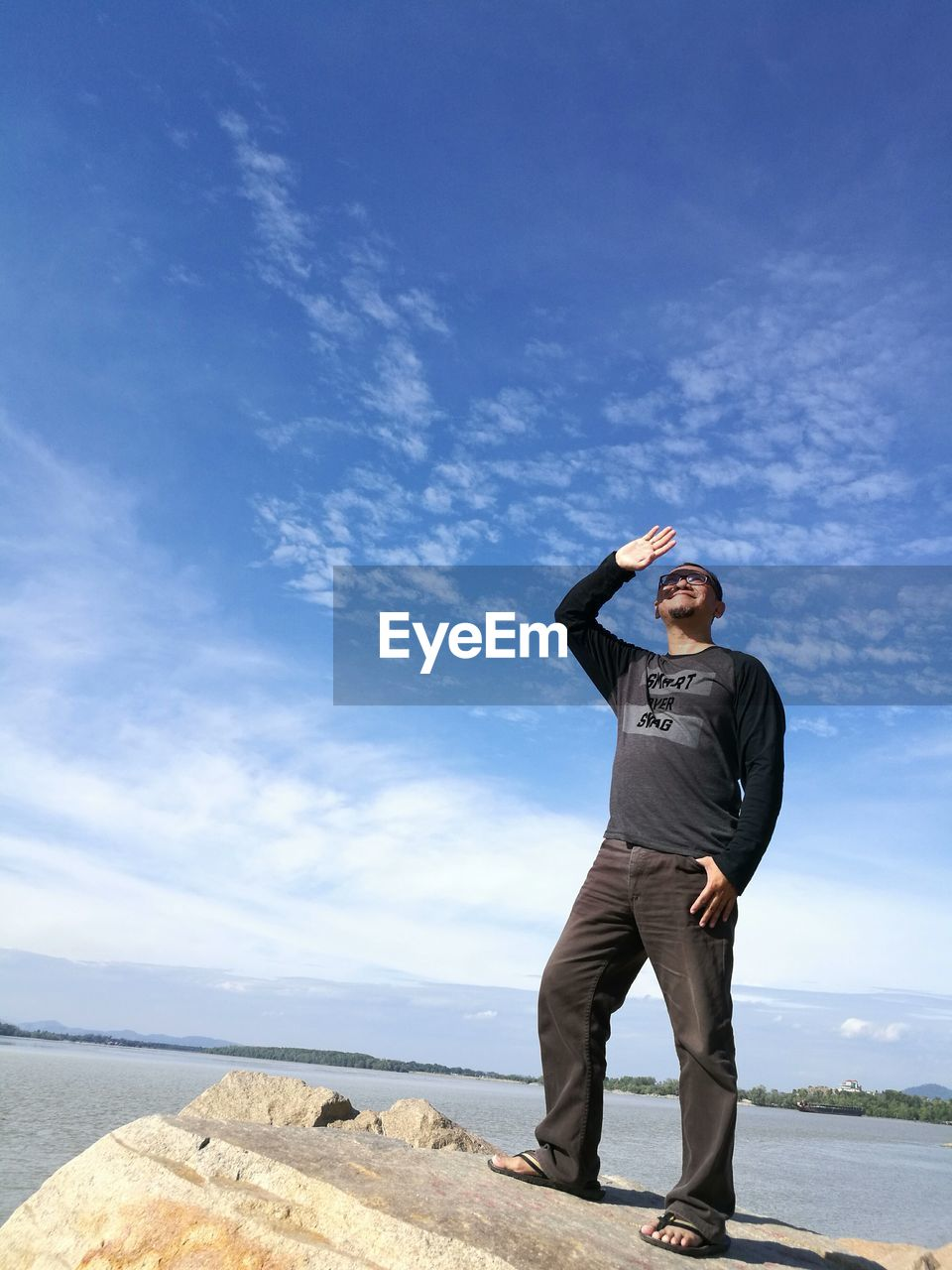 Full Length Of Man Standing On Rock By Lake Against Sky