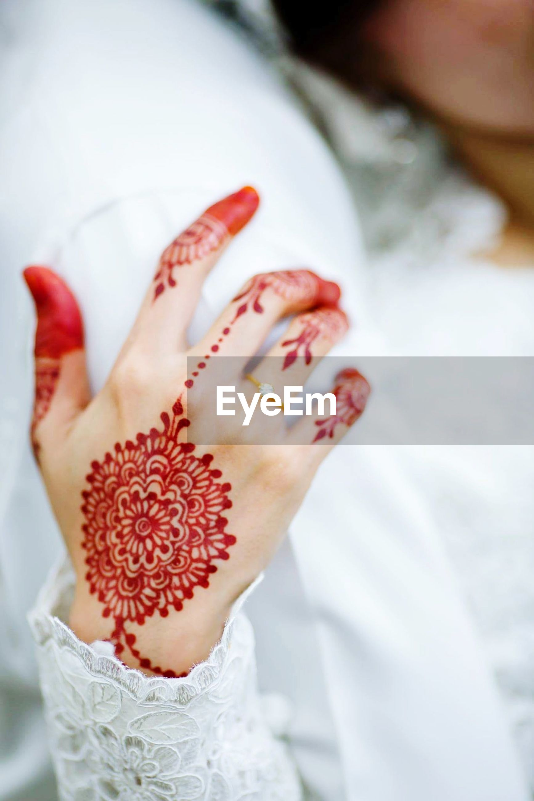 Midsection of groom by bride with henna tattoo