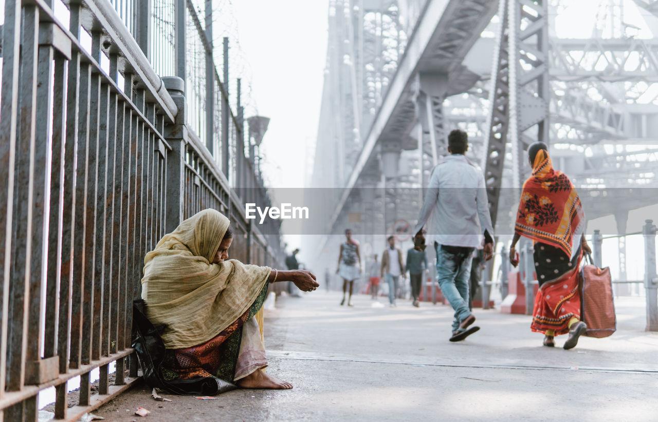 PEOPLE SITTING ON BRIDGE IN CITY