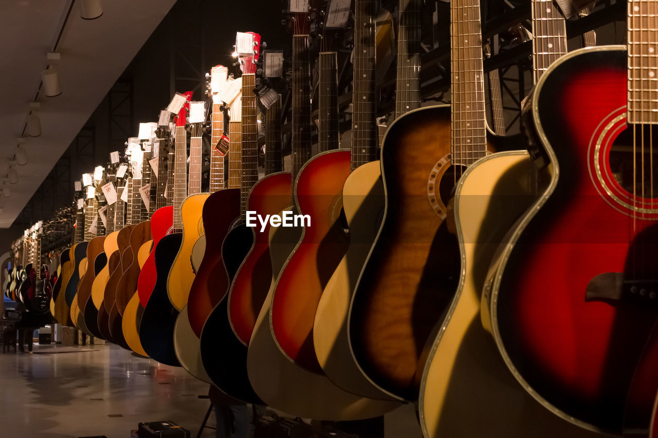 in a row, multi colored, no people, indoors, choice, arrangement, variation, day, arts culture and entertainment, side by side, large group of objects, for sale, hanging, reflection, string instrument, store, shape, close-up, consumerism