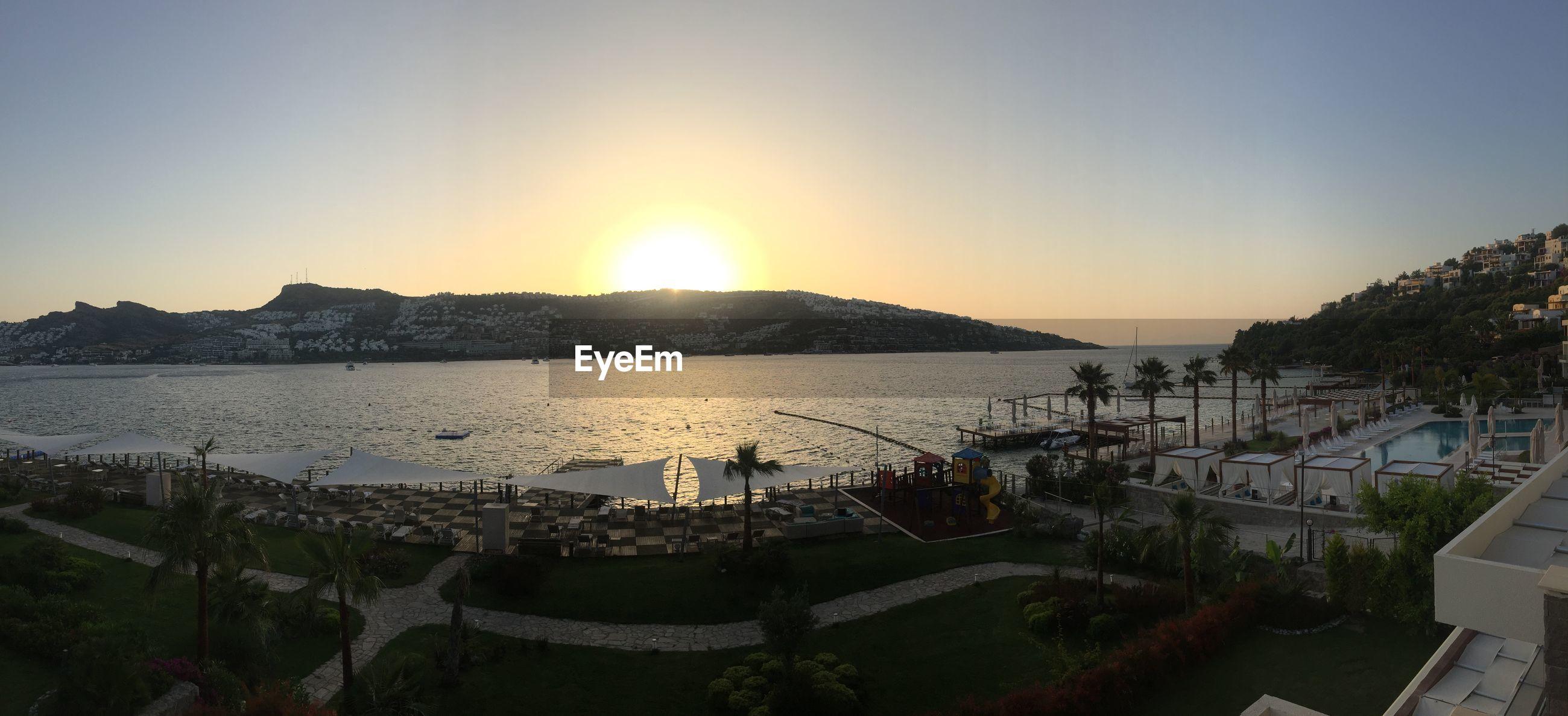 sun, sunset, water, clear sky, tranquil scene, scenics, tranquility, sunlight, beauty in nature, sea, nature, copy space, mountain, idyllic, landscape, beach, sunbeam, sky, lake, outdoors
