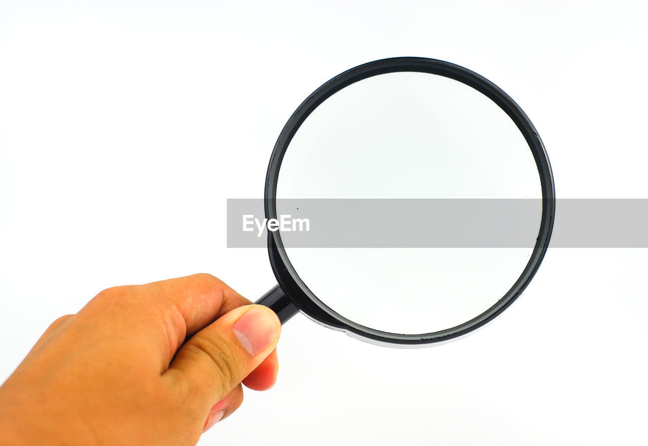 Cropped hand holding magnifying glass against white background