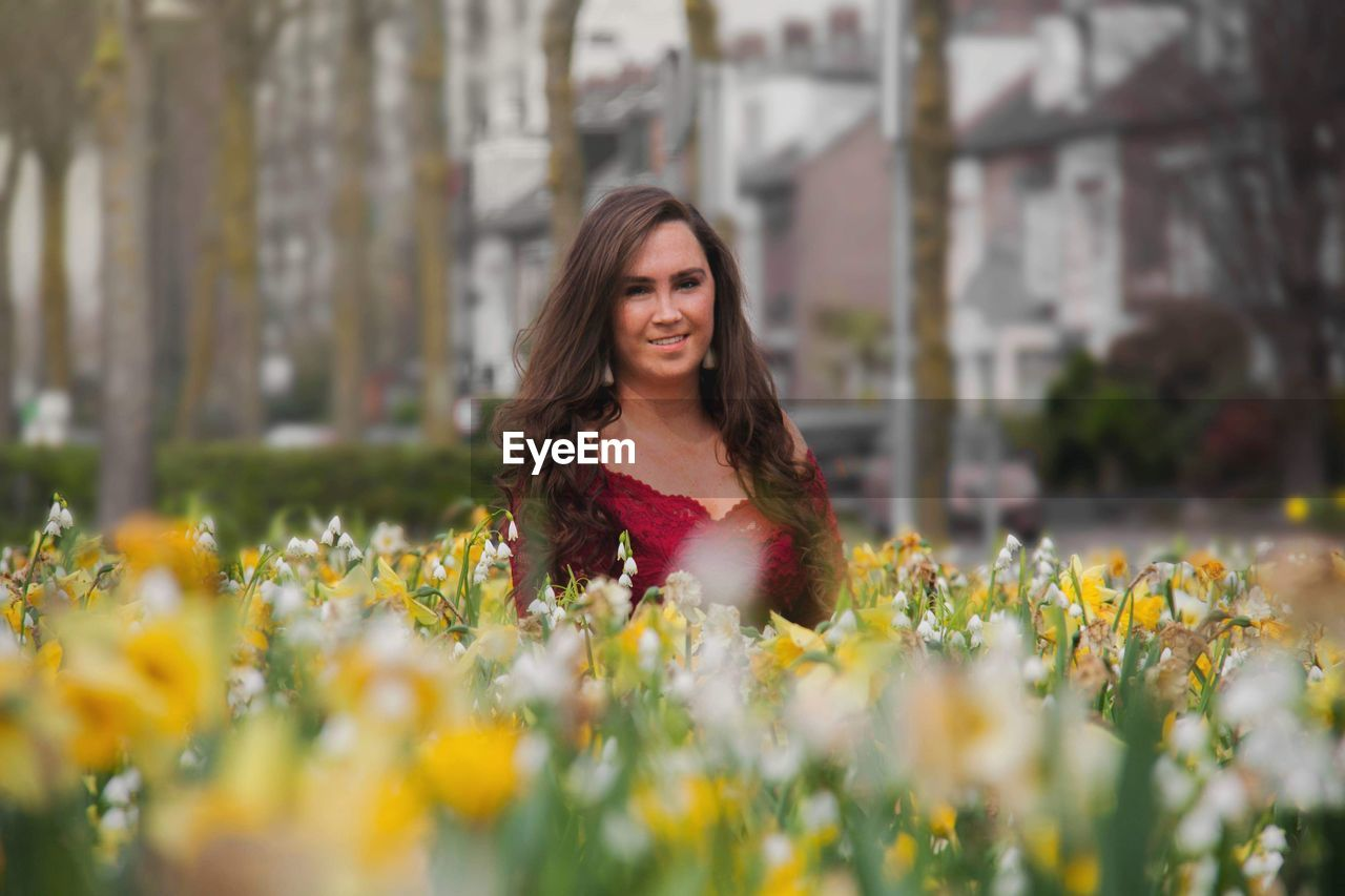 Portrait of smiling woman amidst flowering plants