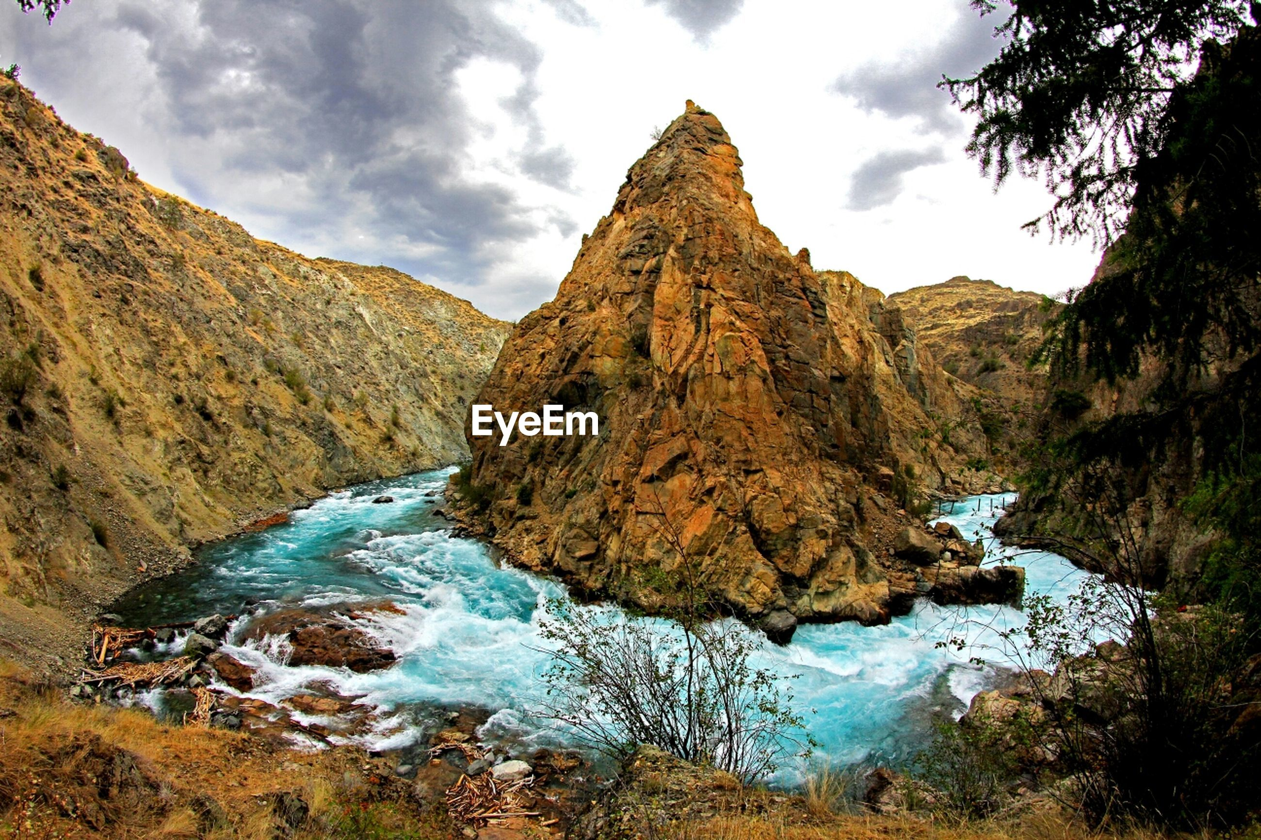 River flowing through rock formations against sky