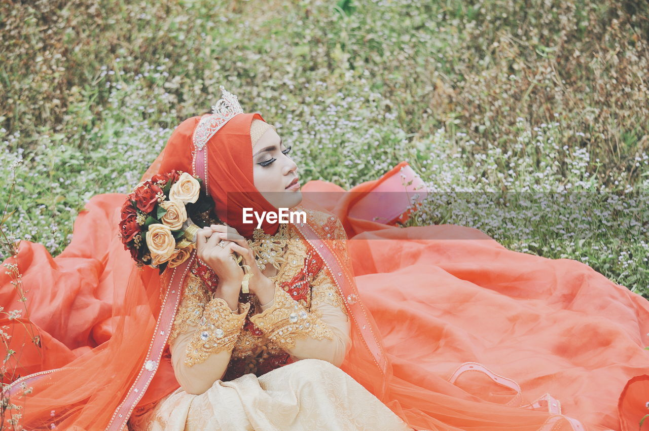 Bride Wearing Wedding Dress While Sitting On Grassy Field At Park