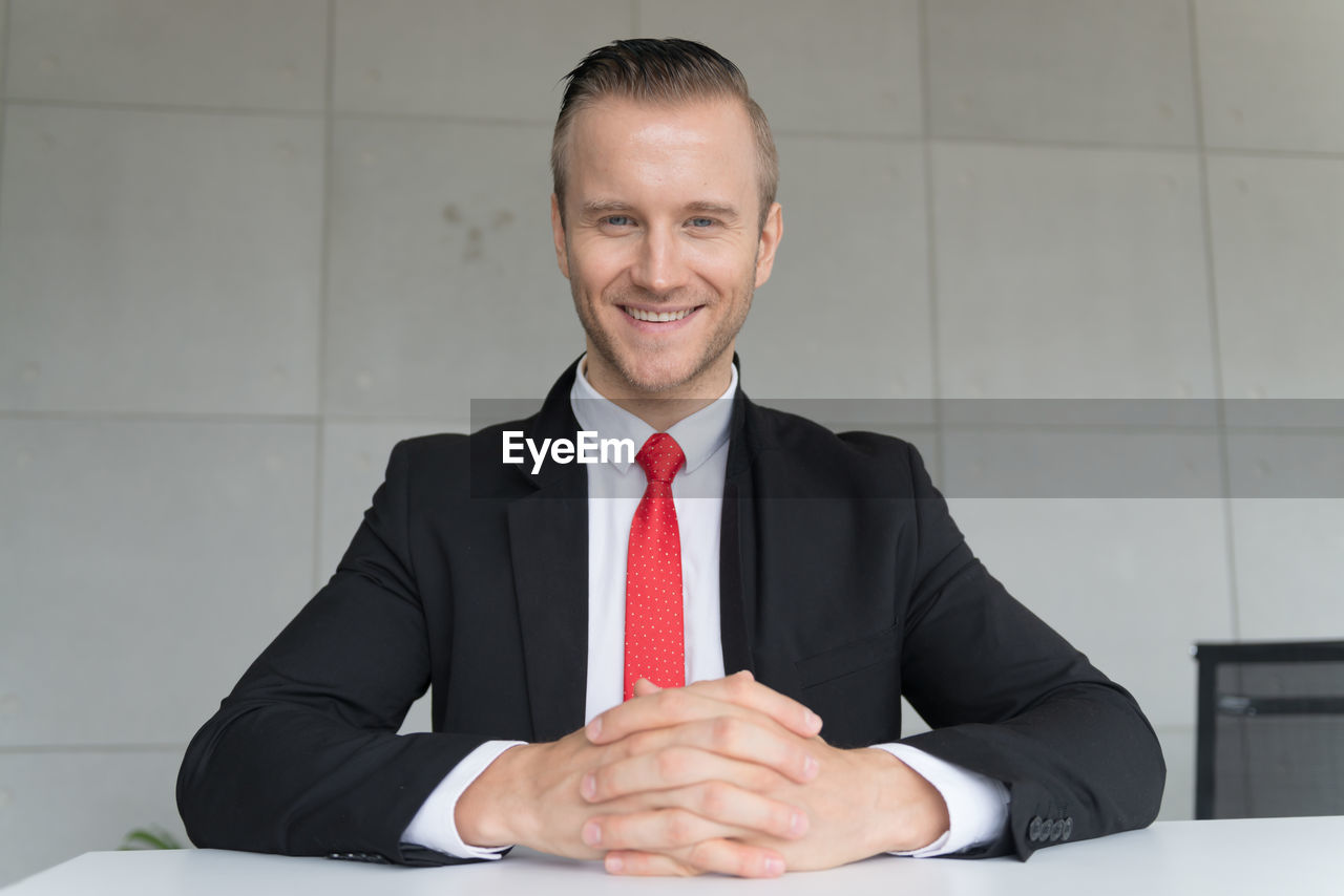 Portrait of smiling businessman with hands clasped sitting at desk against wall in office