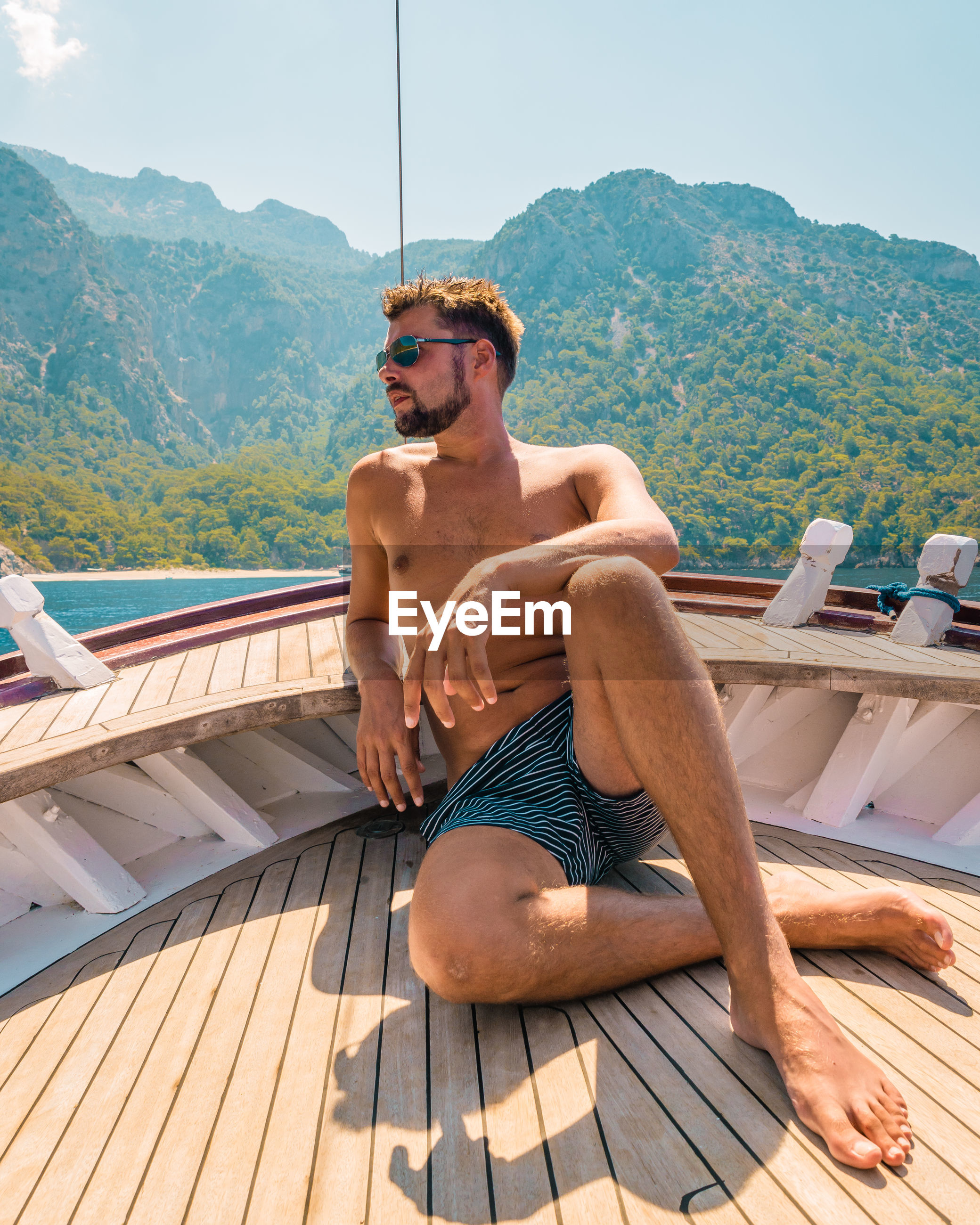Young man sitting in boat against mountain