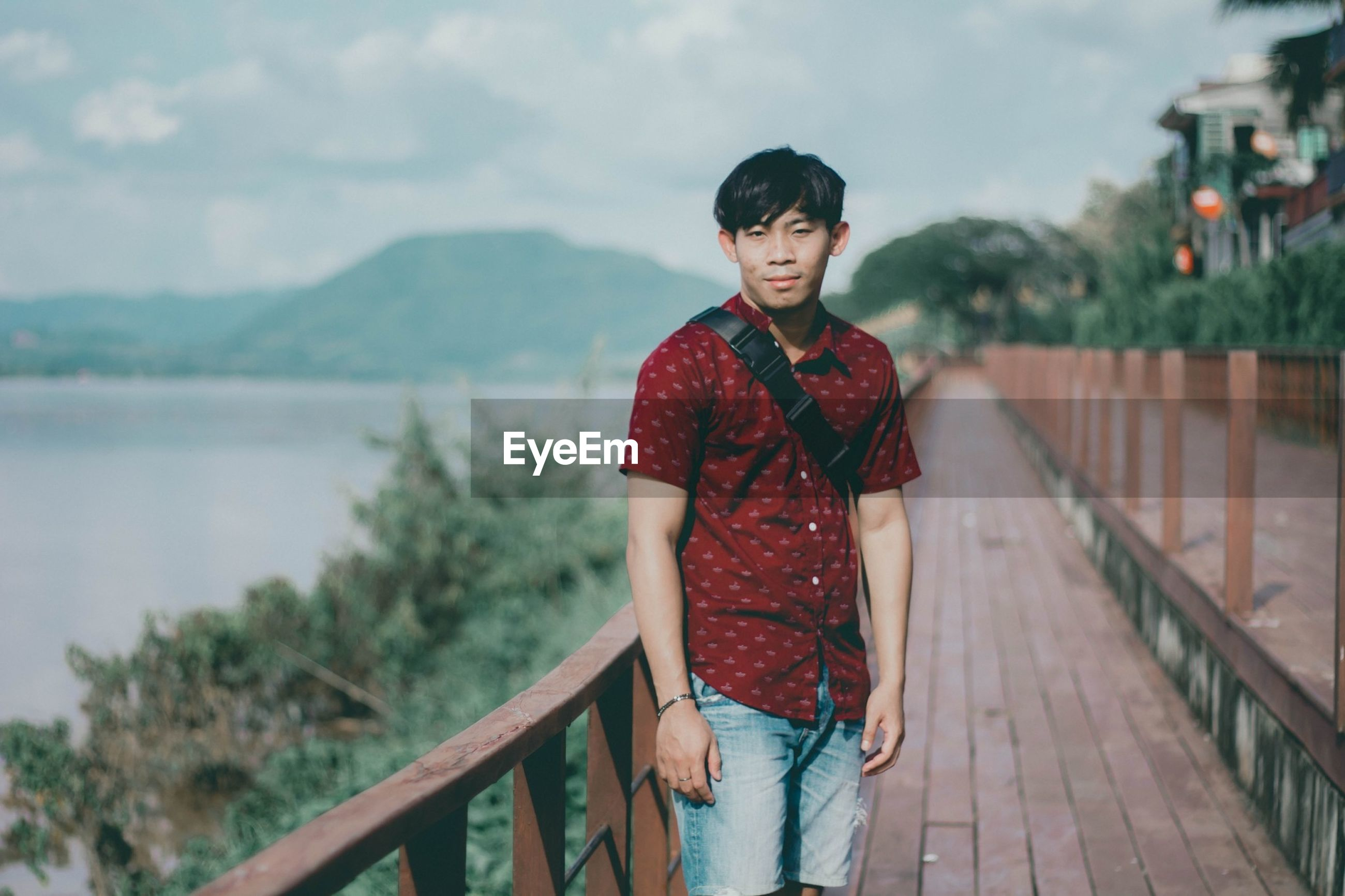 Portrait of young man standing on footbridge