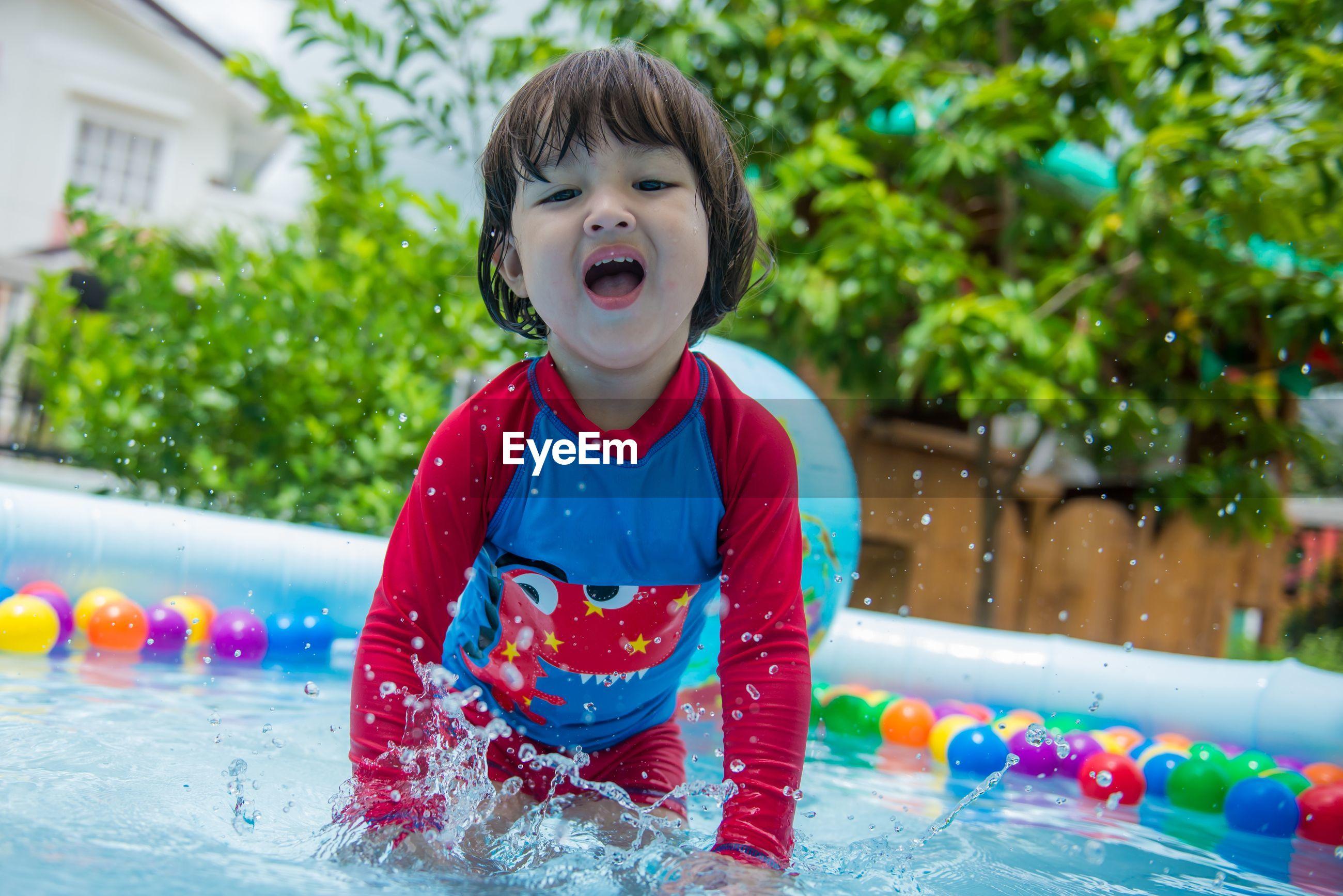 Cute boy playing in swimming pool