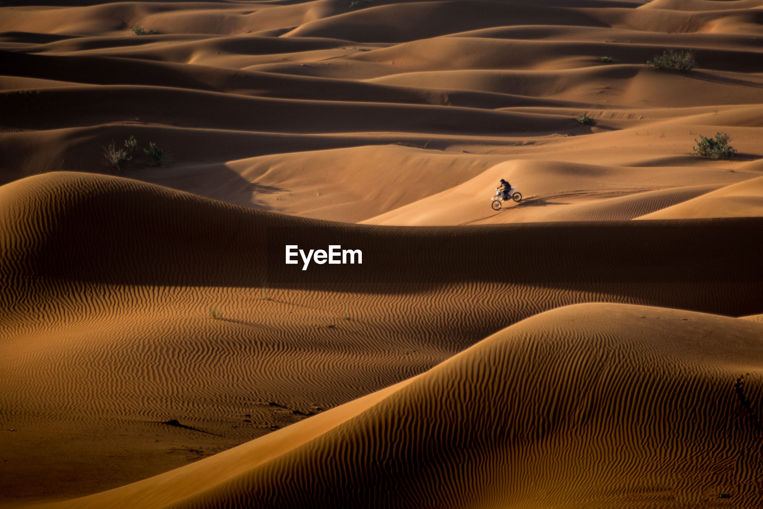 High angle view of man riding motorcycle on sand at desert