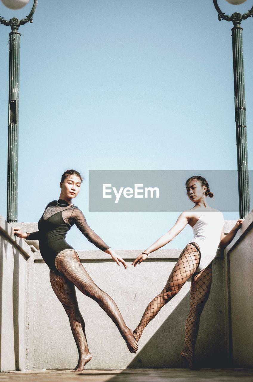 Ballet Dancers In Swimwear Standing Against Clear Sky