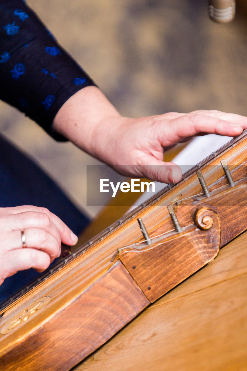 Cropped hands playing zither on table