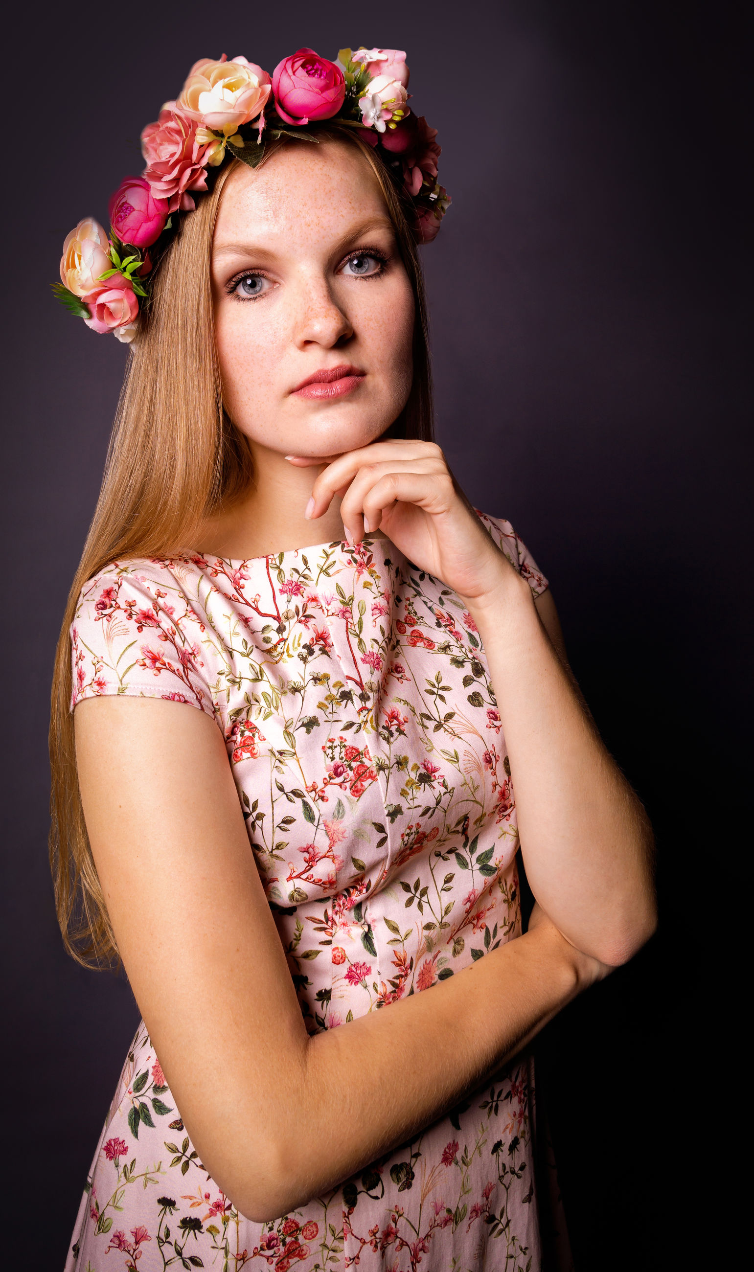 Portrait of beautiful young woman wearing flower tiara against gray background
