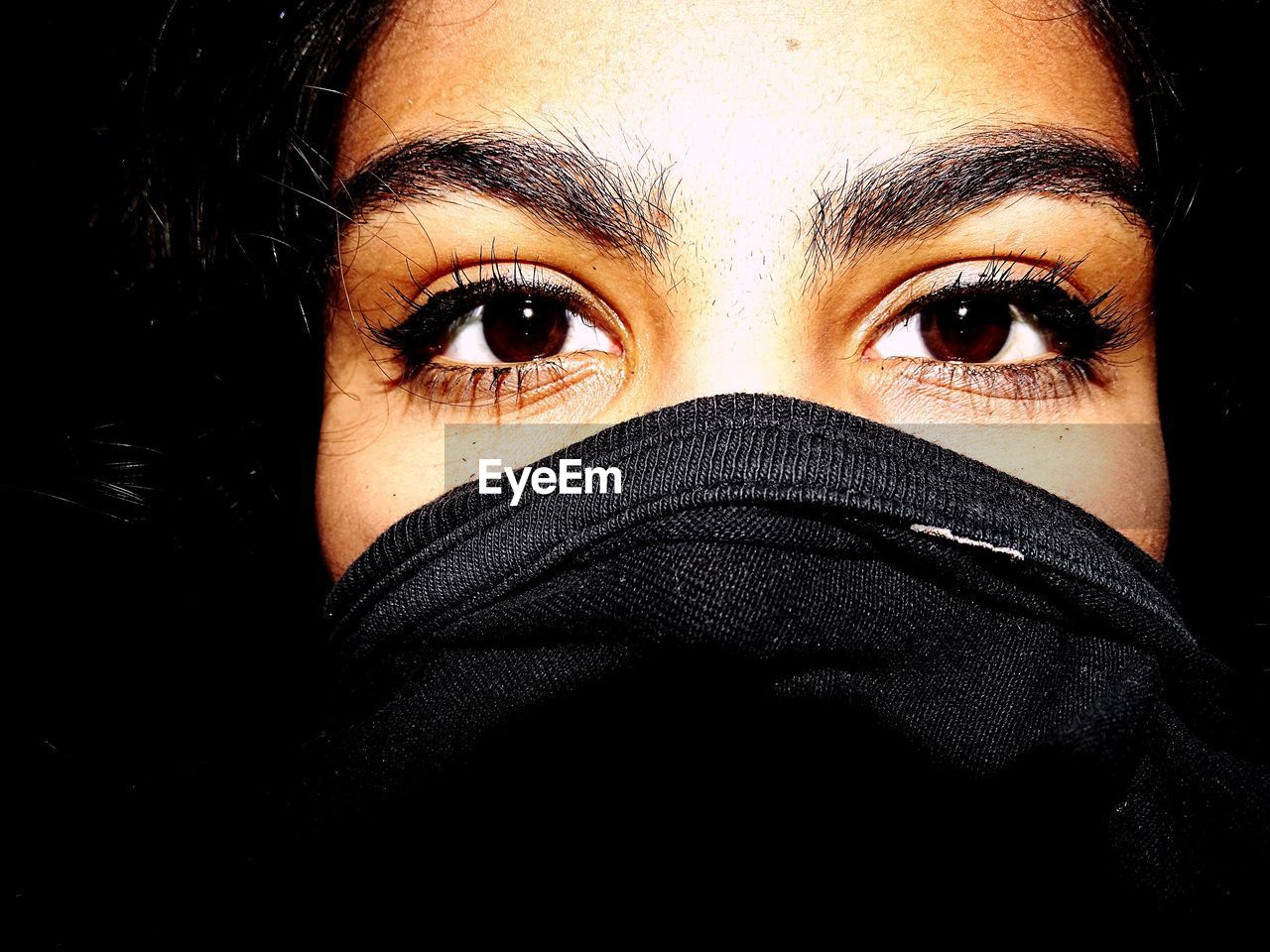looking at camera, portrait, human face, one person, human body part, headshot, body part, young adult, human eye, close-up, covering, eye, front view, adult, real people, indoors, studio shot, lifestyles, young women, black background, obscured face, scarf, eyebrow, hands covering mouth, beautiful woman