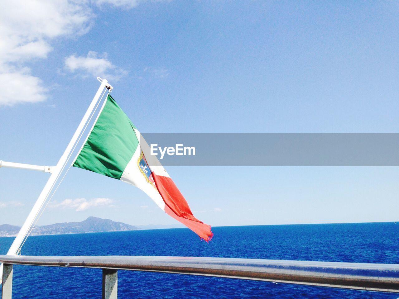 Flag by sea against sky