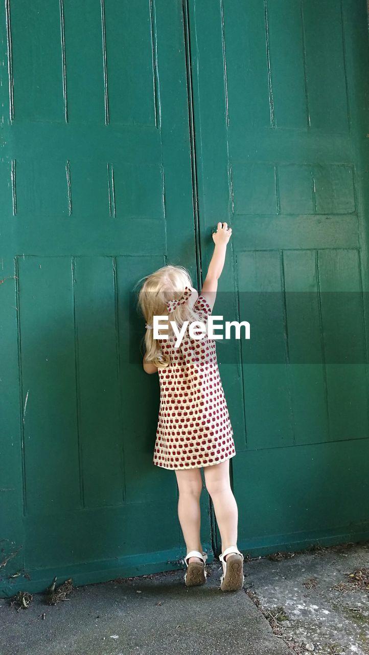 Rear View Of Girl Opening Green Door
