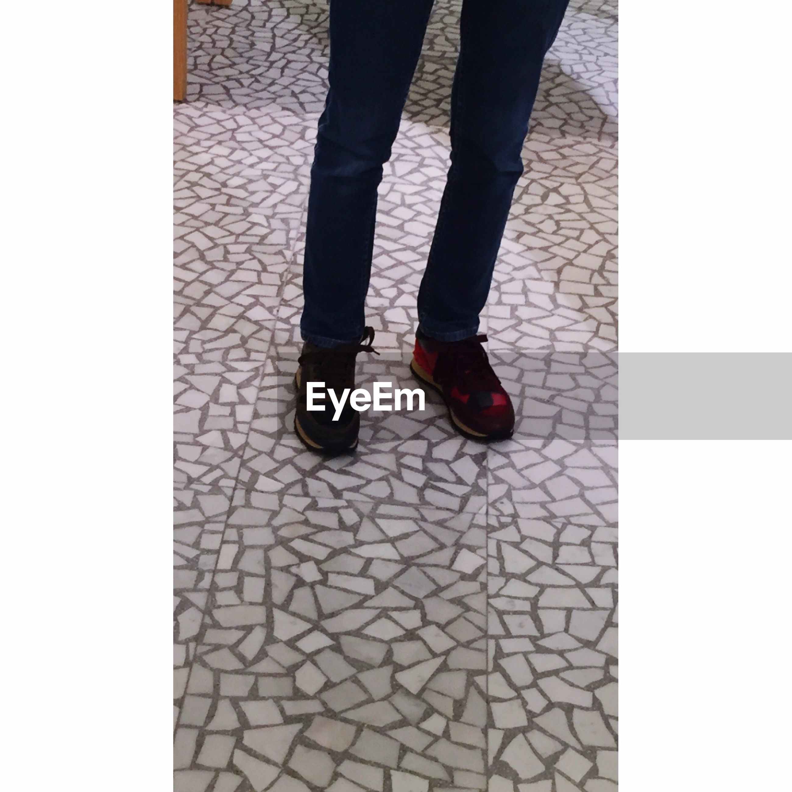 low section, person, shoe, standing, lifestyles, human foot, men, footwear, jeans, transfer print, walking, leisure activity, auto post production filter, unrecognizable person, tiled floor, paving stone