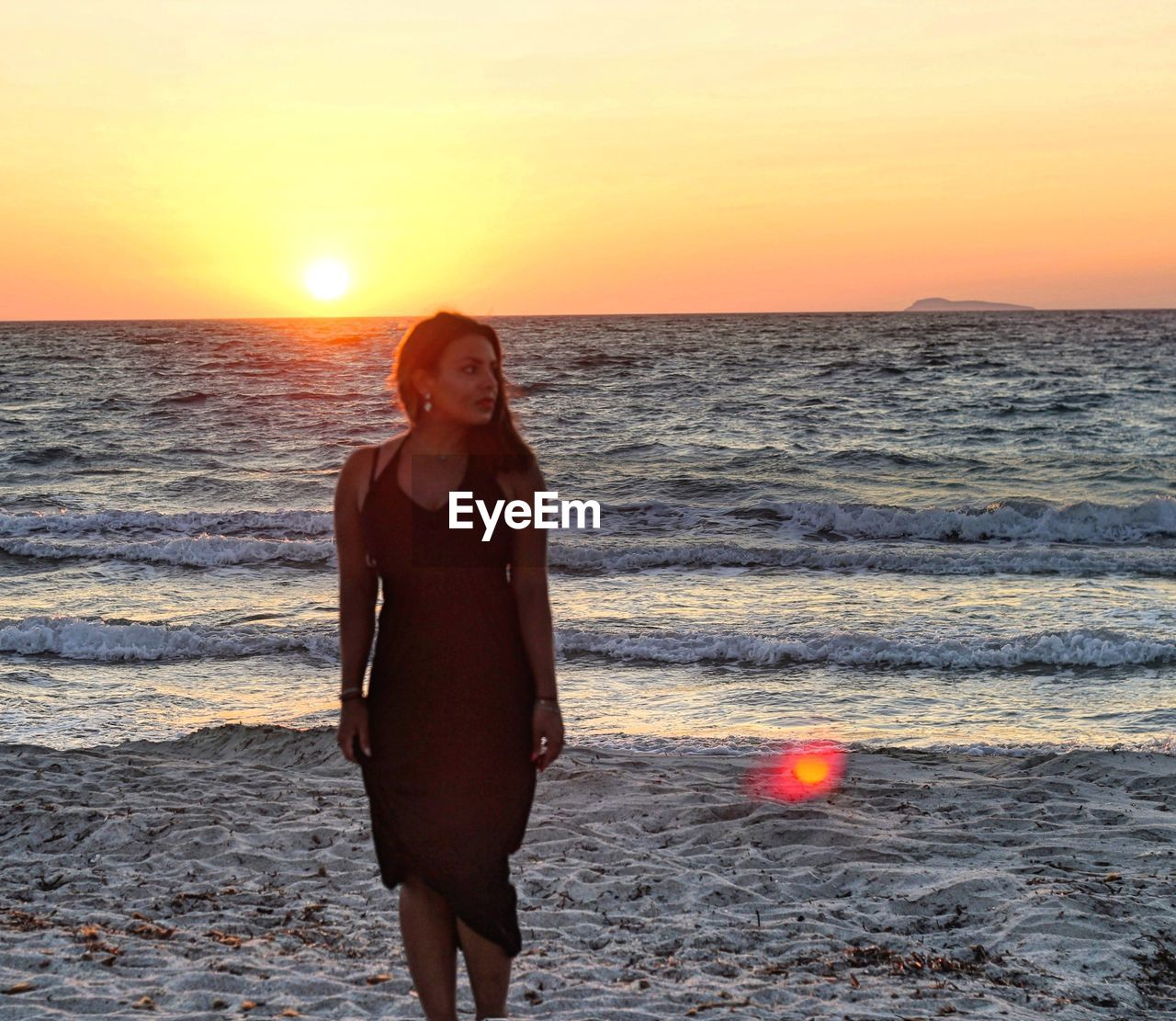 Woman looking away while standing at beach against sky during sunset