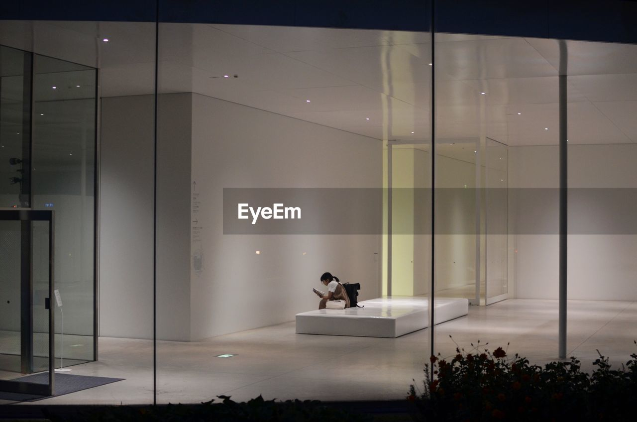 real people, indoors, glass - material, one person, sitting, modern, transparent, office, architecture, illuminated, lifestyles, one animal, lighting equipment, business, adult, men, built structure, luxury