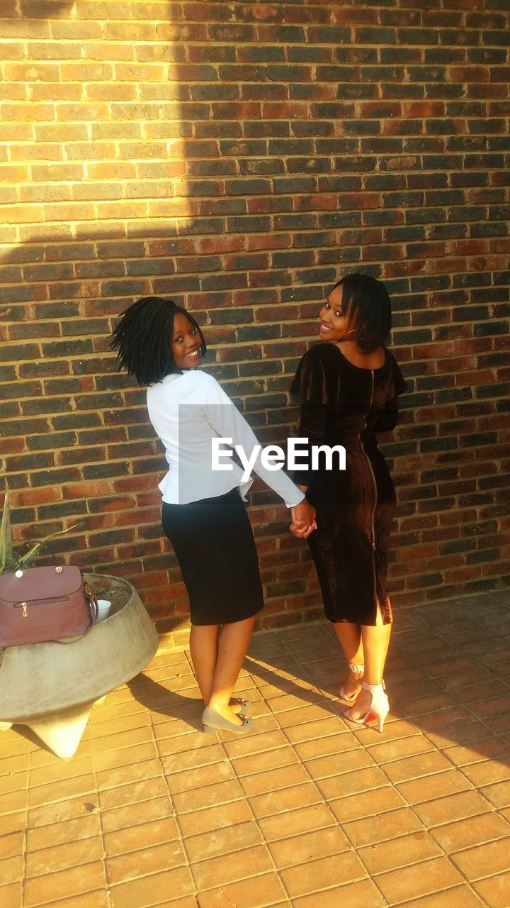 two people, brick wall, real people, full length, togetherness, love, casual clothing, lifestyles, standing, leisure activity, bonding, day, indoors, friendship, young women, young adult