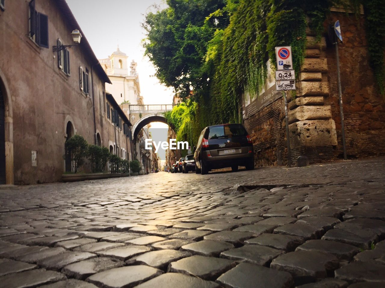 architecture, land vehicle, car, built structure, transportation, building exterior, cobblestone, mode of transport, street, outdoors, day, stationary, no people, tree, city, sky