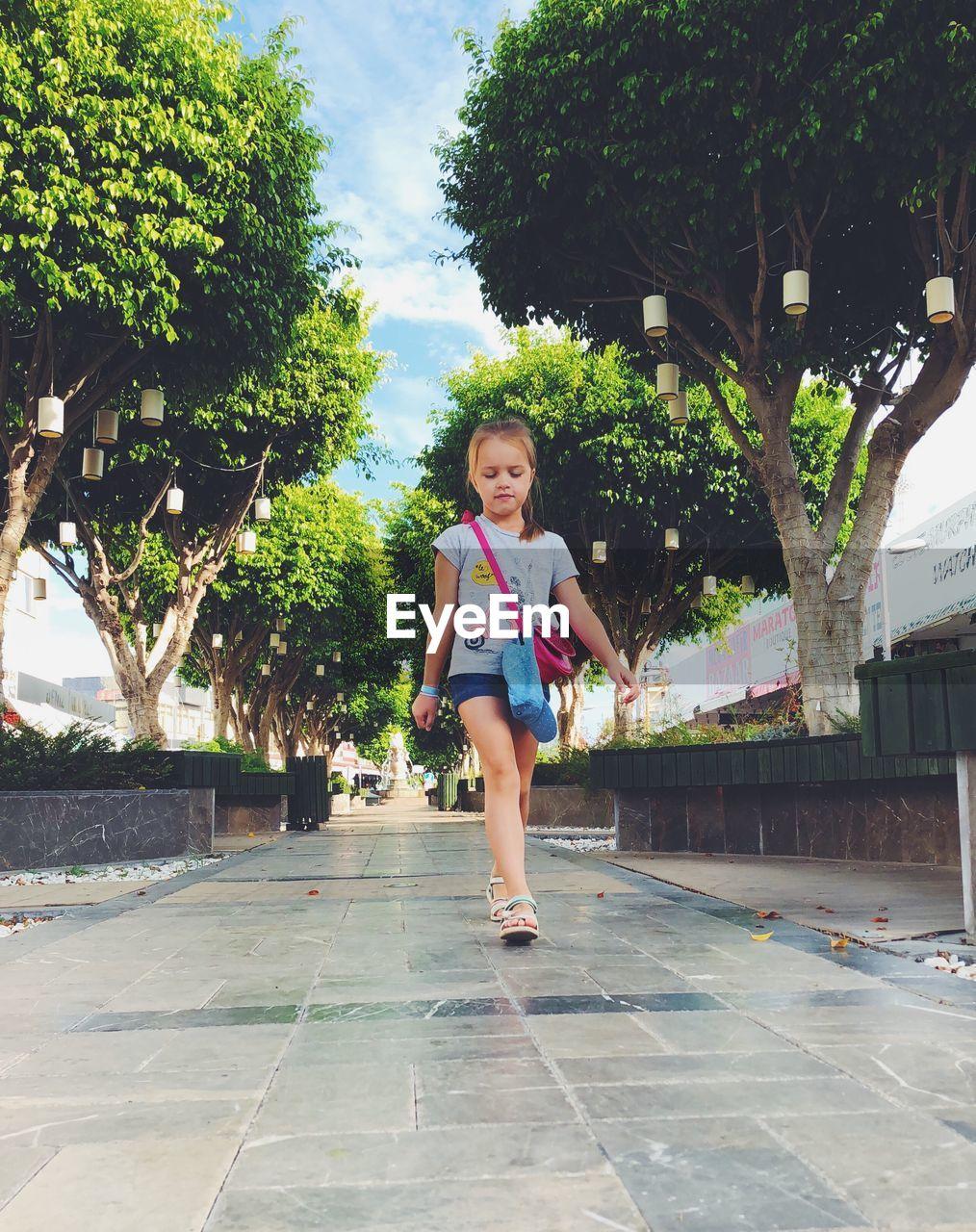 Girl Walking On Footpath