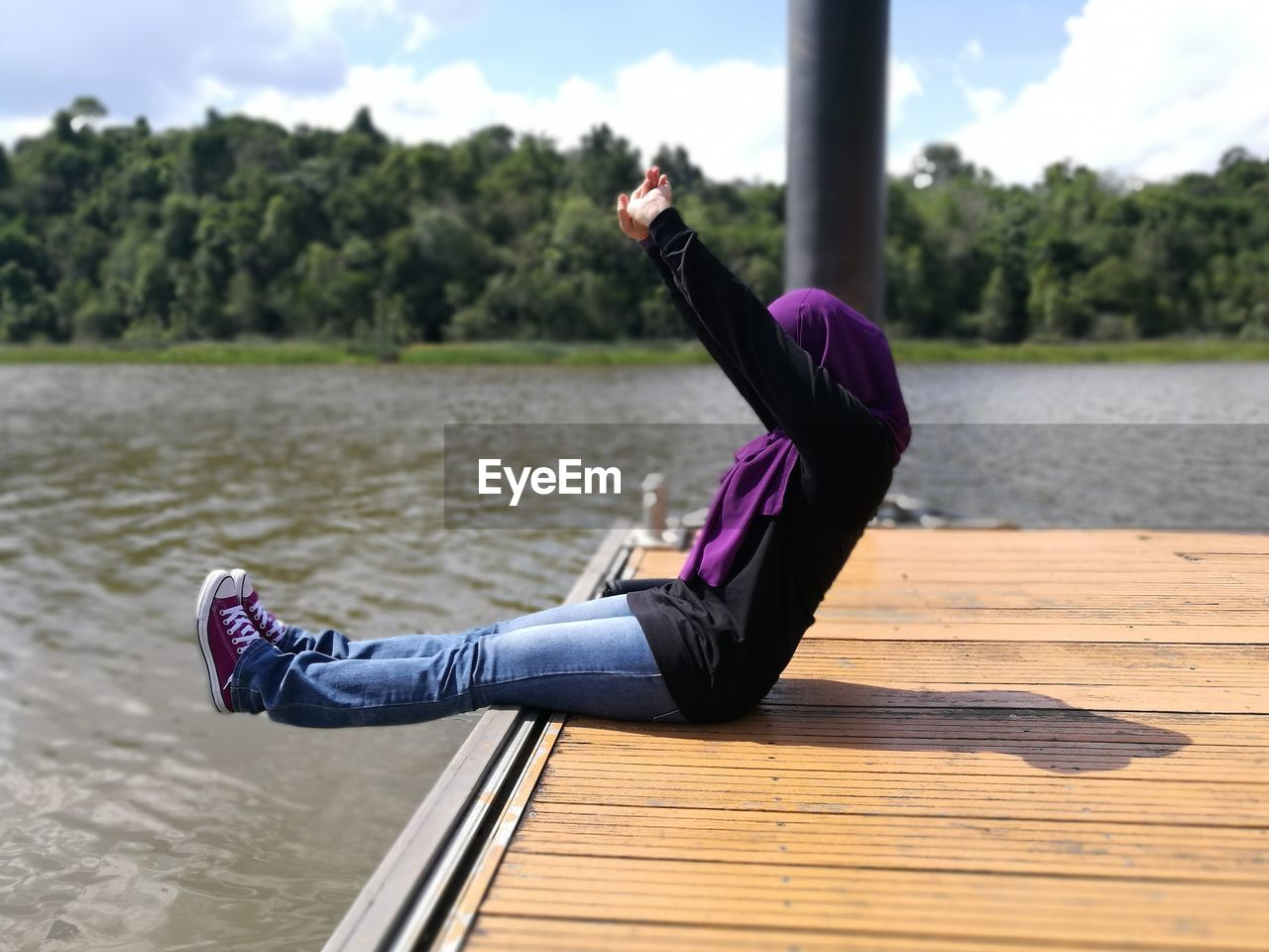 Side view of mid adult woman with arms raised sitting on pier over lake