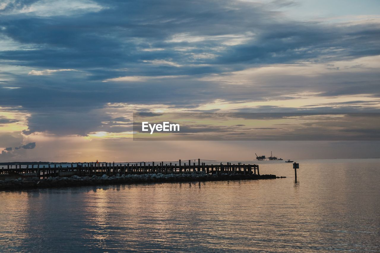 cloud - sky, sky, water, sunset, waterfront, sea, architecture, beauty in nature, scenics - nature, no people, pier, nature, tranquil scene, built structure, tranquility, outdoors, transportation, industry, building exterior