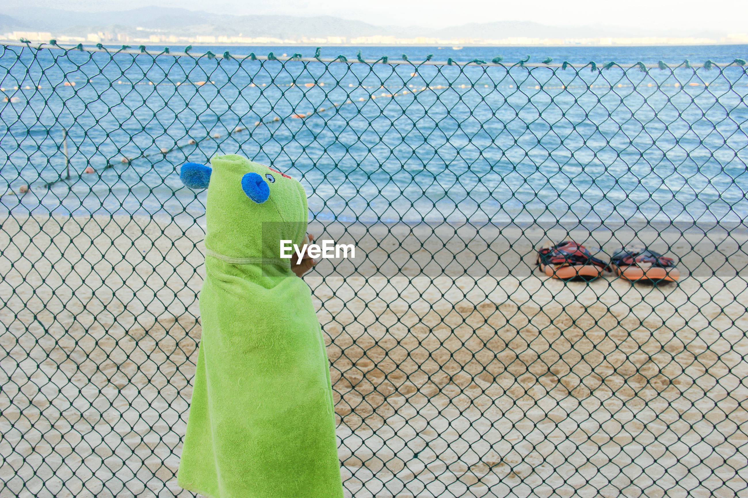 Girl wearing costume standing by chainlink fence against sea