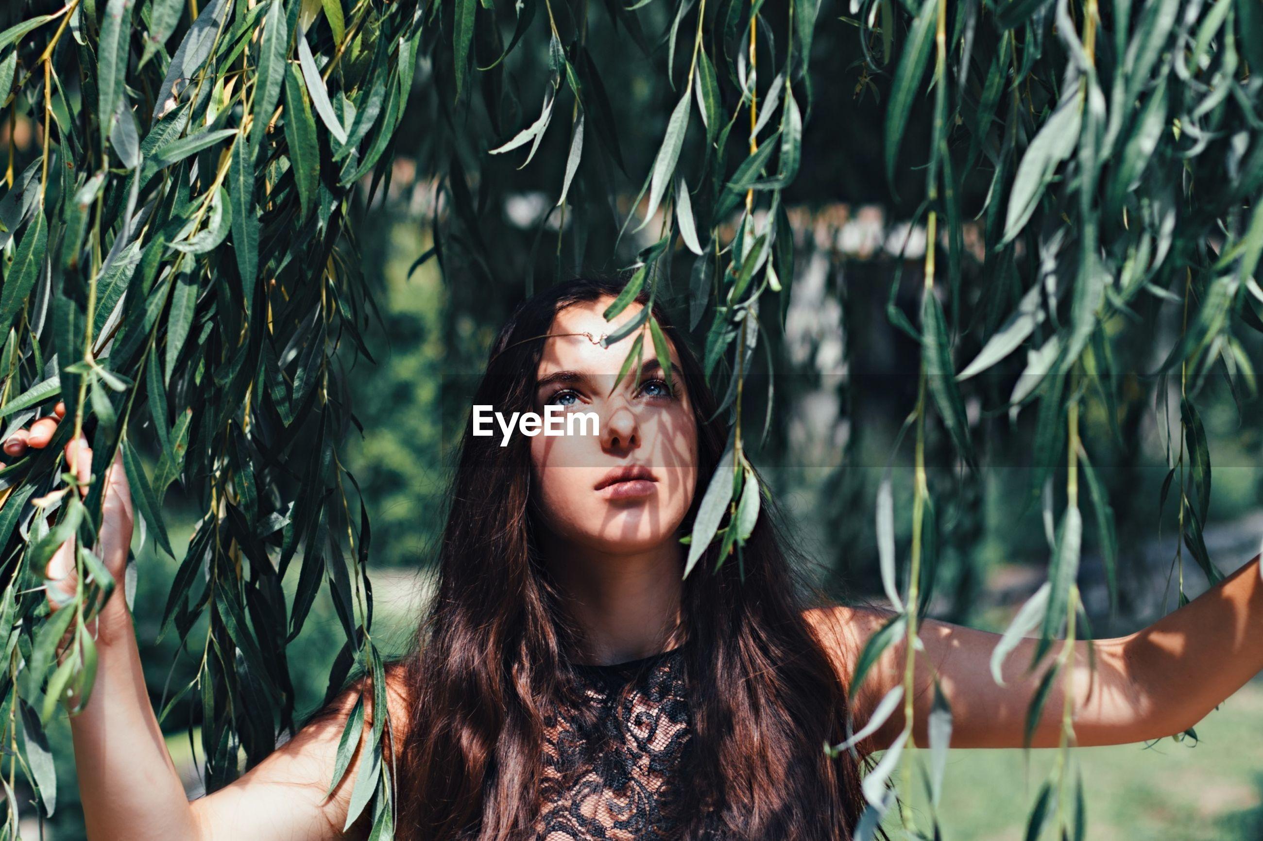 Attractive woman in lush foliage