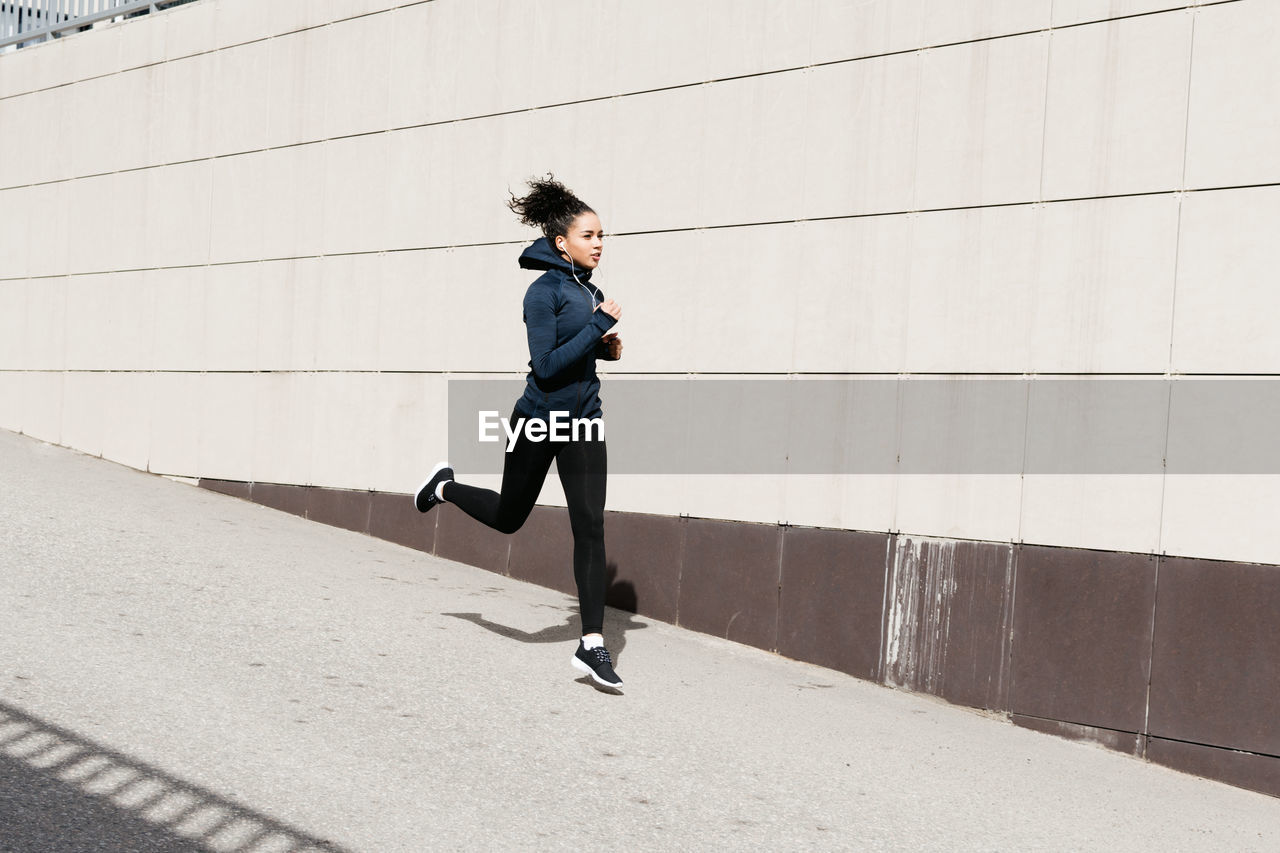 Woman Jogging On Footpath By Wall