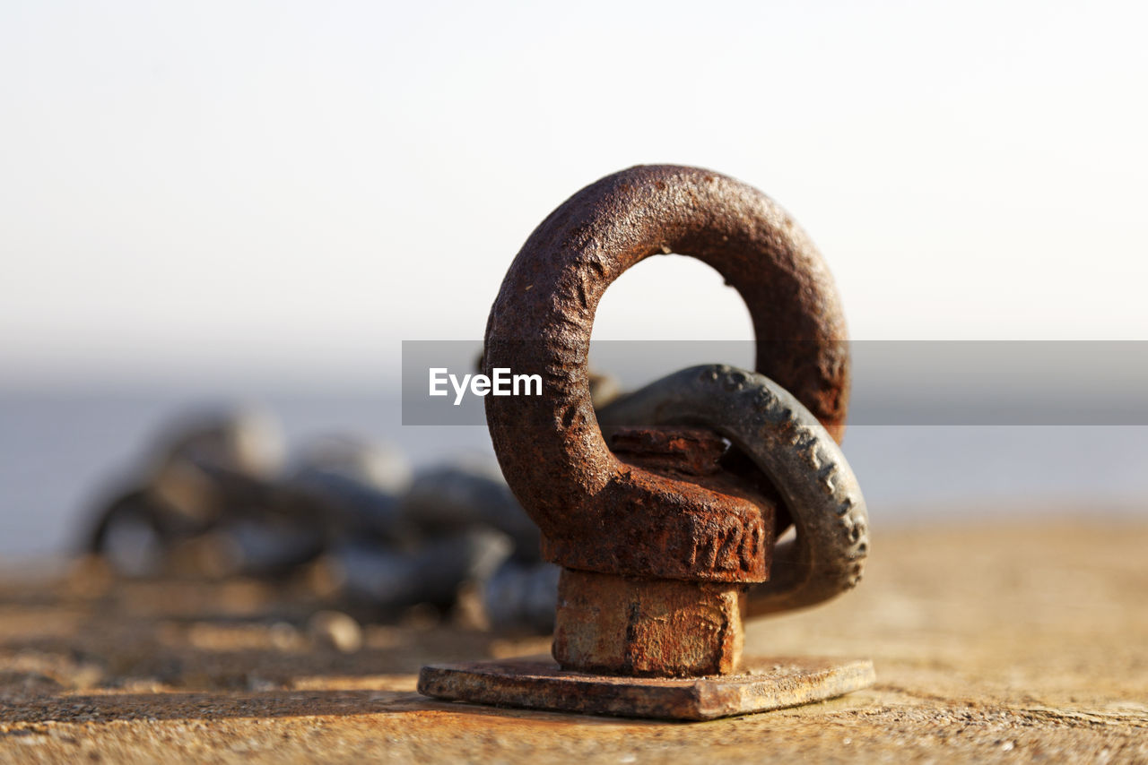 CLOSE-UP OF RUSTY CHAIN ON BEACH AGAINST SKY