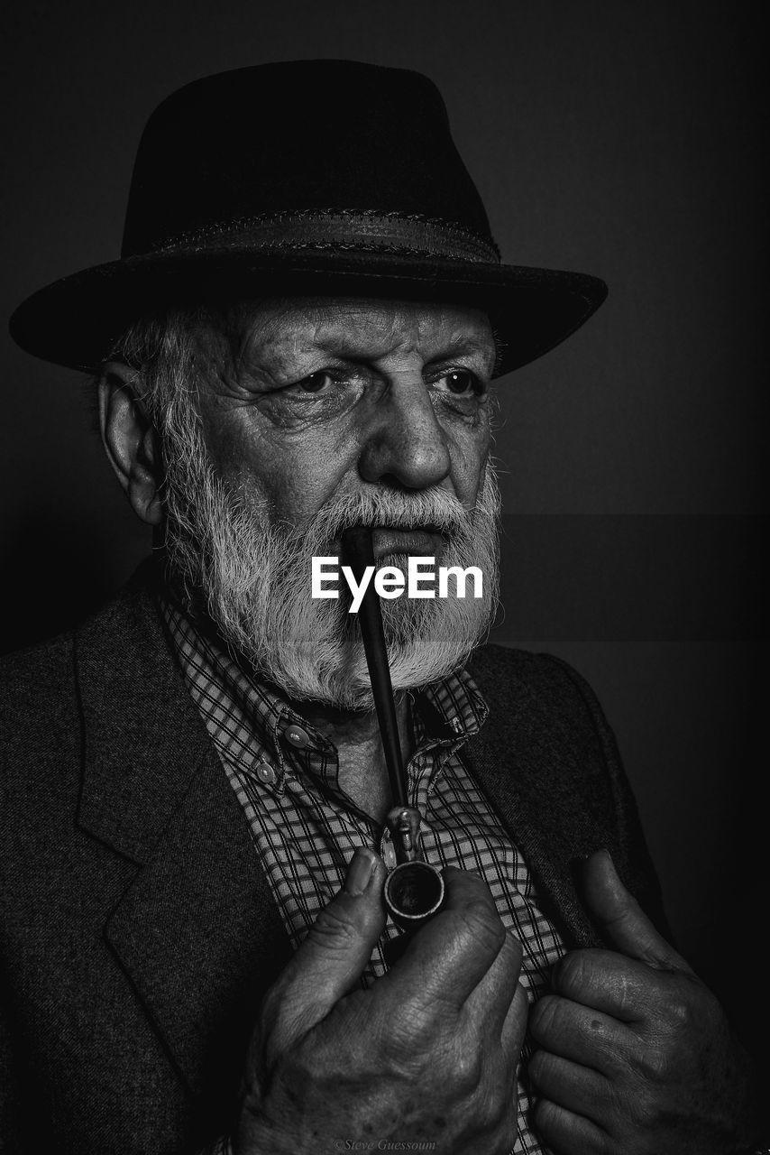 Man Smoking Pipe Cigarette Against Black Background